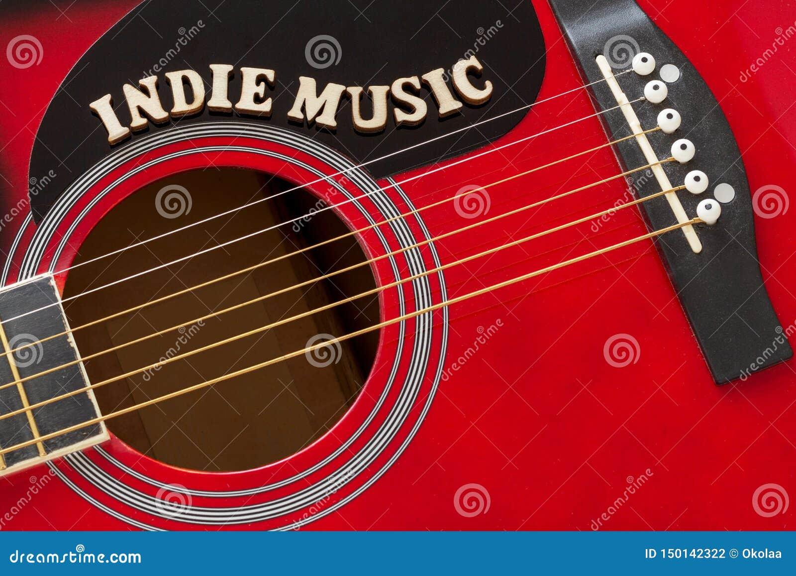 Wort-Indie Musik mit hölzernen Buchstaben, Nahaufnahme auf einer Oberfläche der roten Akustikgitarre Musikunterhaltungshintergrun