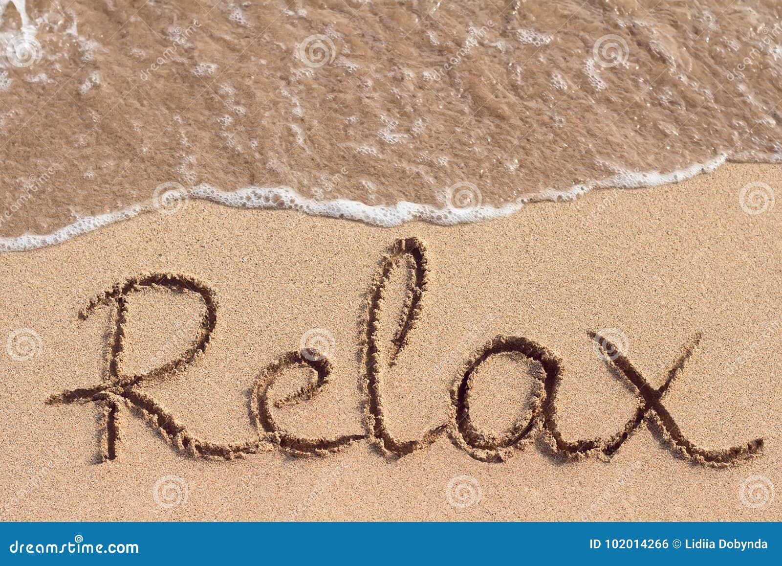 Wort Relax ist die Hand, die auf den Strand geschrieben wird