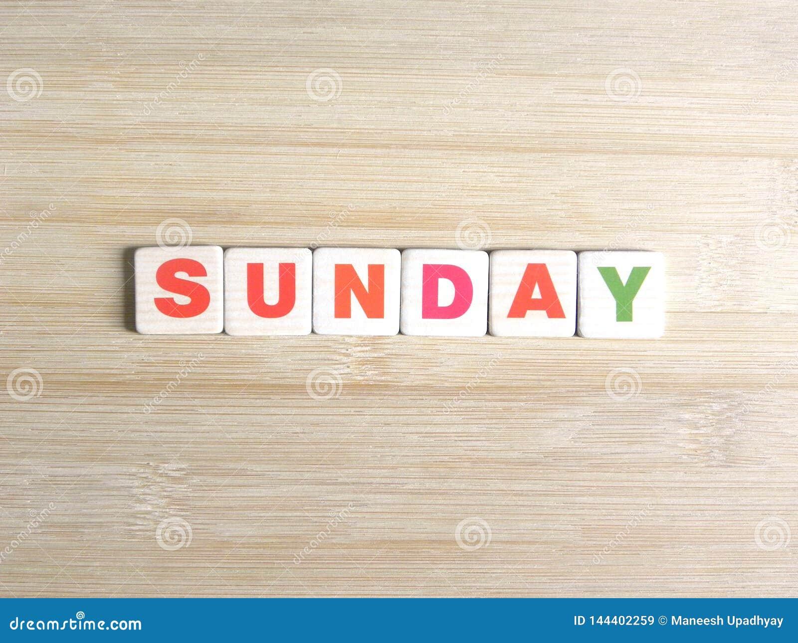 Wort Sonntag auf hölzernem Hintergrund