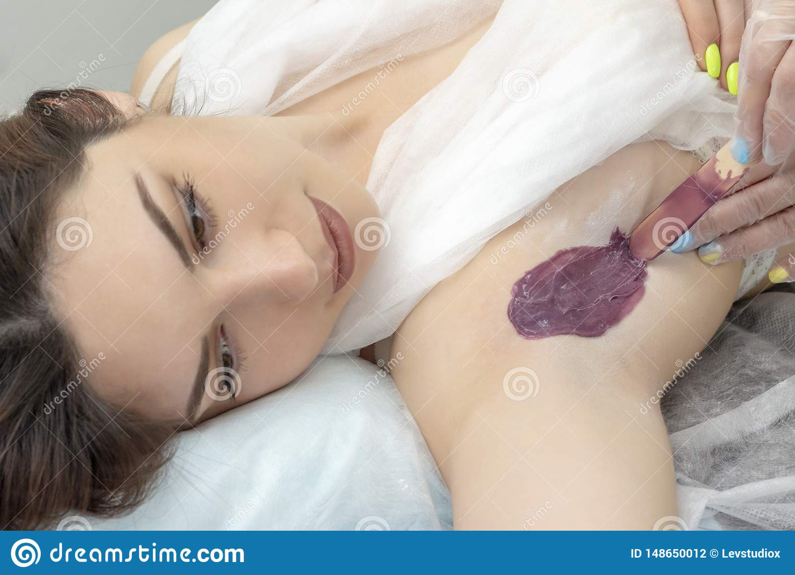 Wosk depilacji dziewczyna nawoskuje pi?knego dziewczyny lying on the beach na le?ance w zdroju centrum robi nawoskuj?cy procedur?