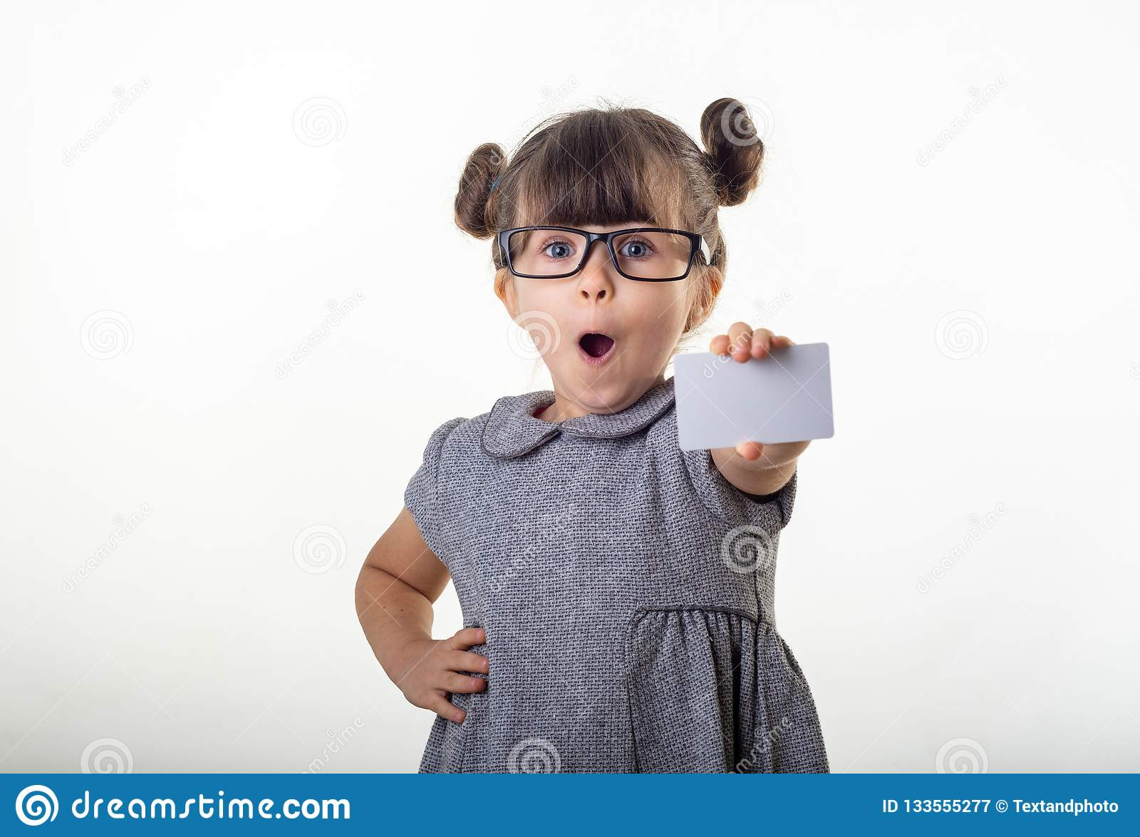 Wow! Happy shocked child holding discount white card in her hands. Surprised kid with credit card.