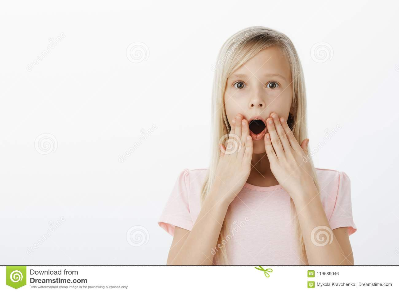 Wow, kid shocked hearing amazing news about favorite cartoon. Indoor shot of amazed and surprised happy blond daughter