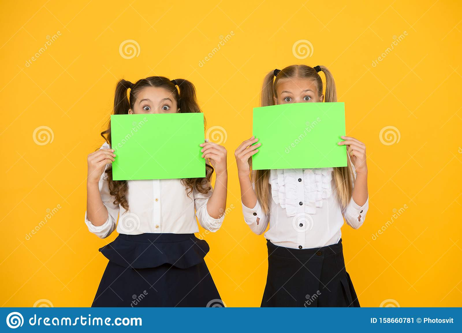 Wow. Little girls holding empty sheets of paper on yellow background. Small children with blank green school paper for