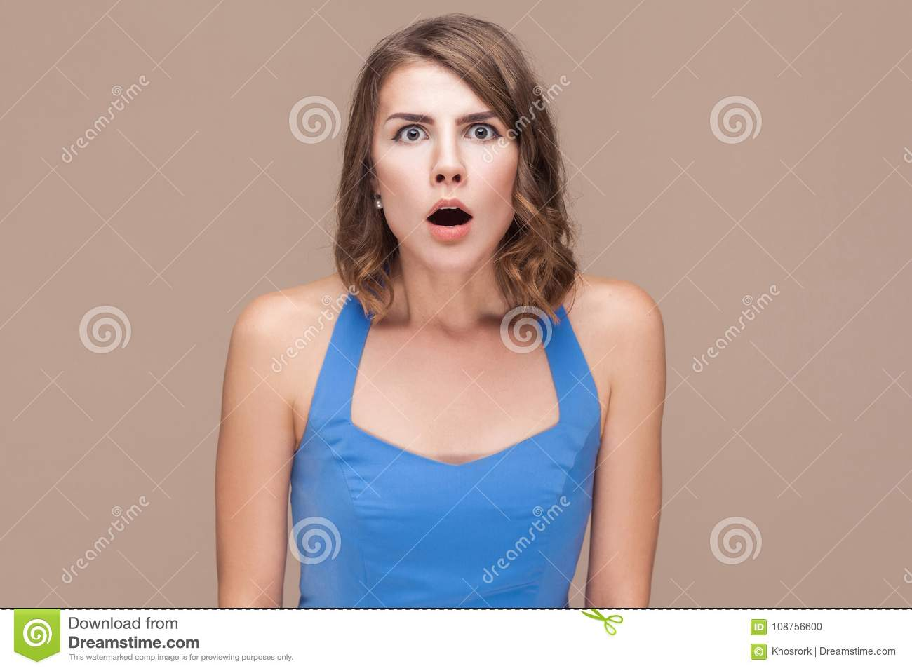 Wow! Shocked woman with big eyes looking at camera.