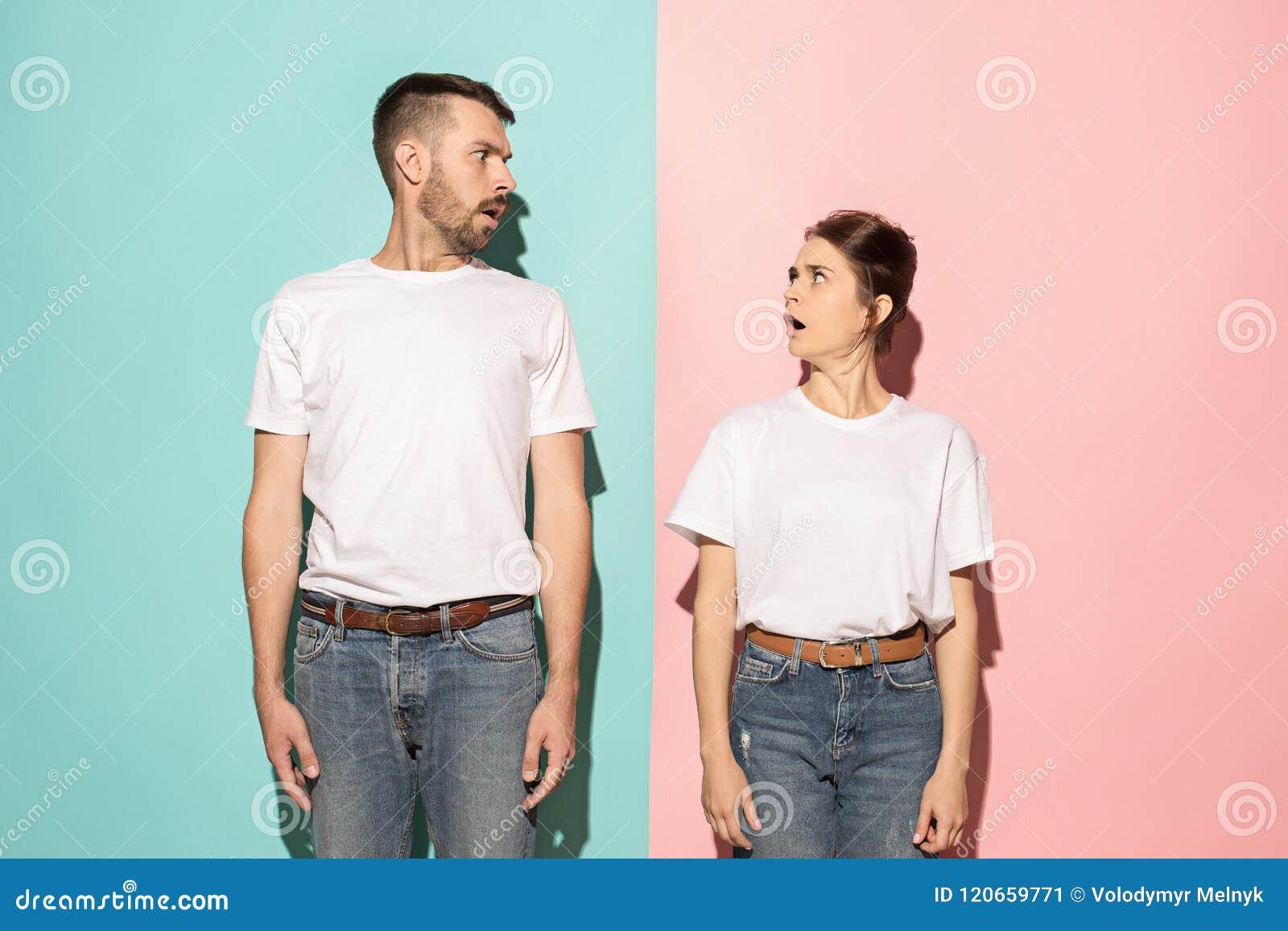Wow Twijfelachtig peinzend paar met nadenkende uitdrukking die keus maken tegen roze achtergrond