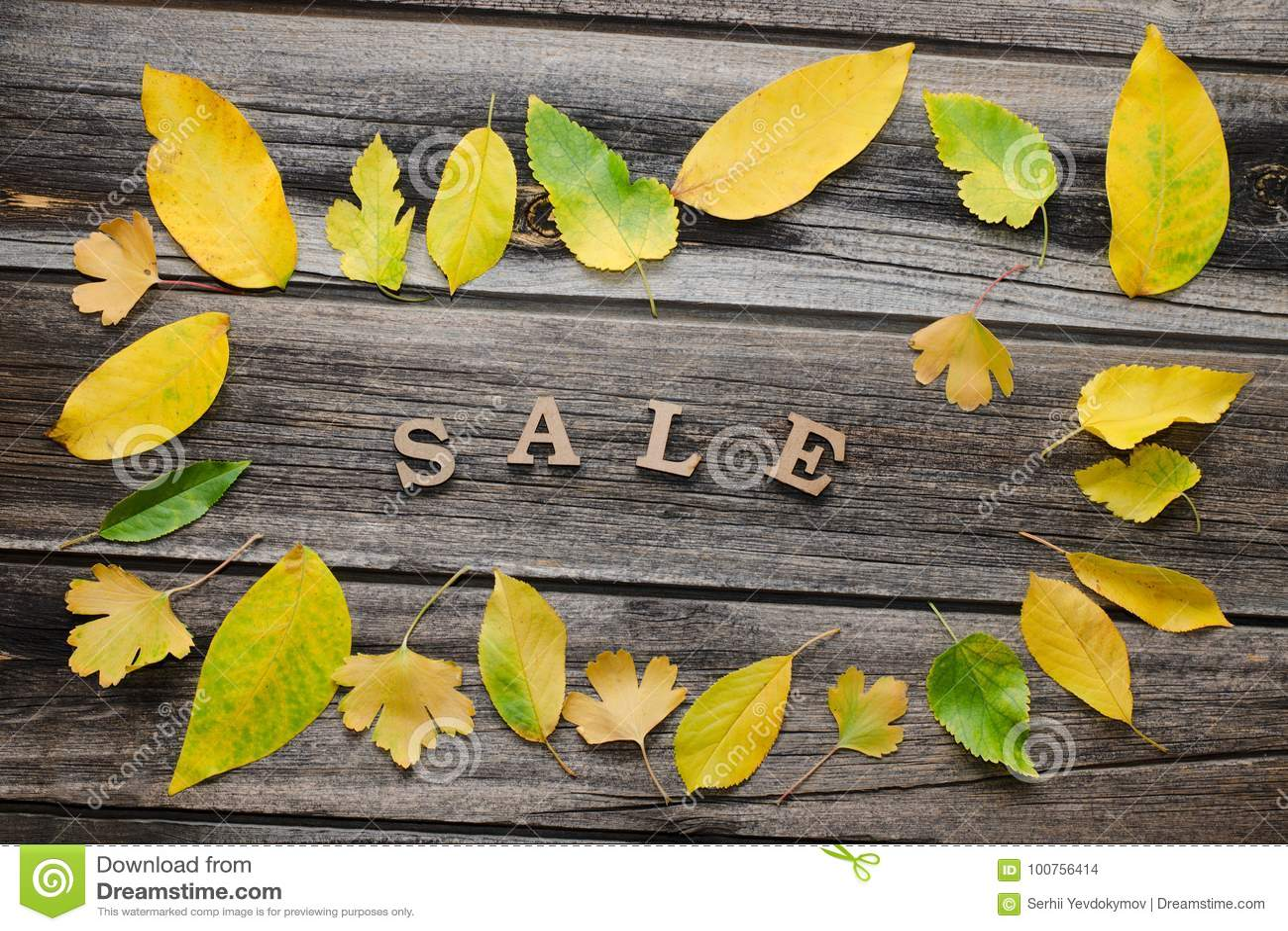 Wpisowa sprzedaż na drewnianym tle, rama żółci liście