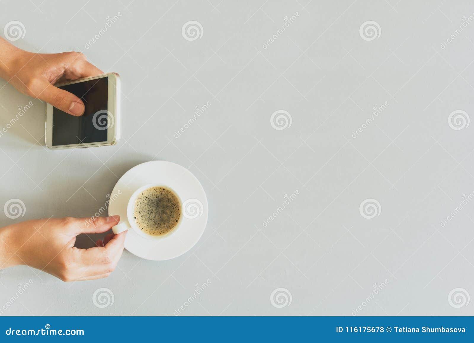 Wręcza kobiety używa mądrze telefon na popielatym drewnianym stole kawa więcej czasu Ranku rytuał