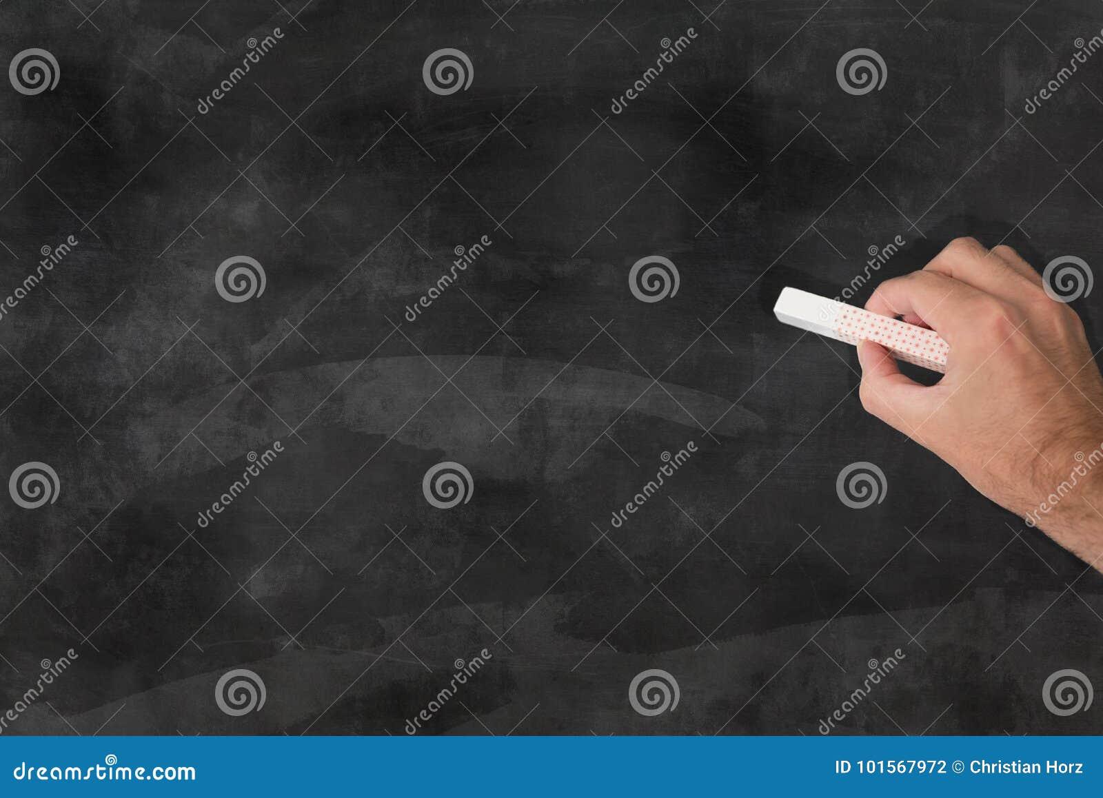 Wręcza trzymać kawałek kreda przed chalkboard