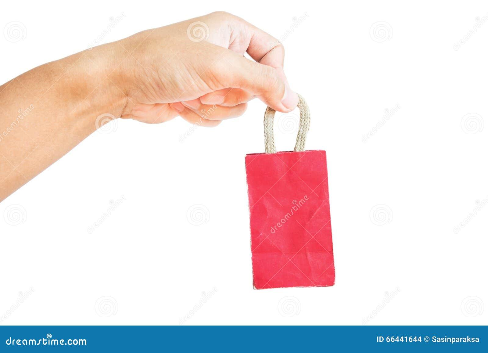 Wręcza trzymać małego czerwonego torba na zakupy, odizolowywającego na białym tle