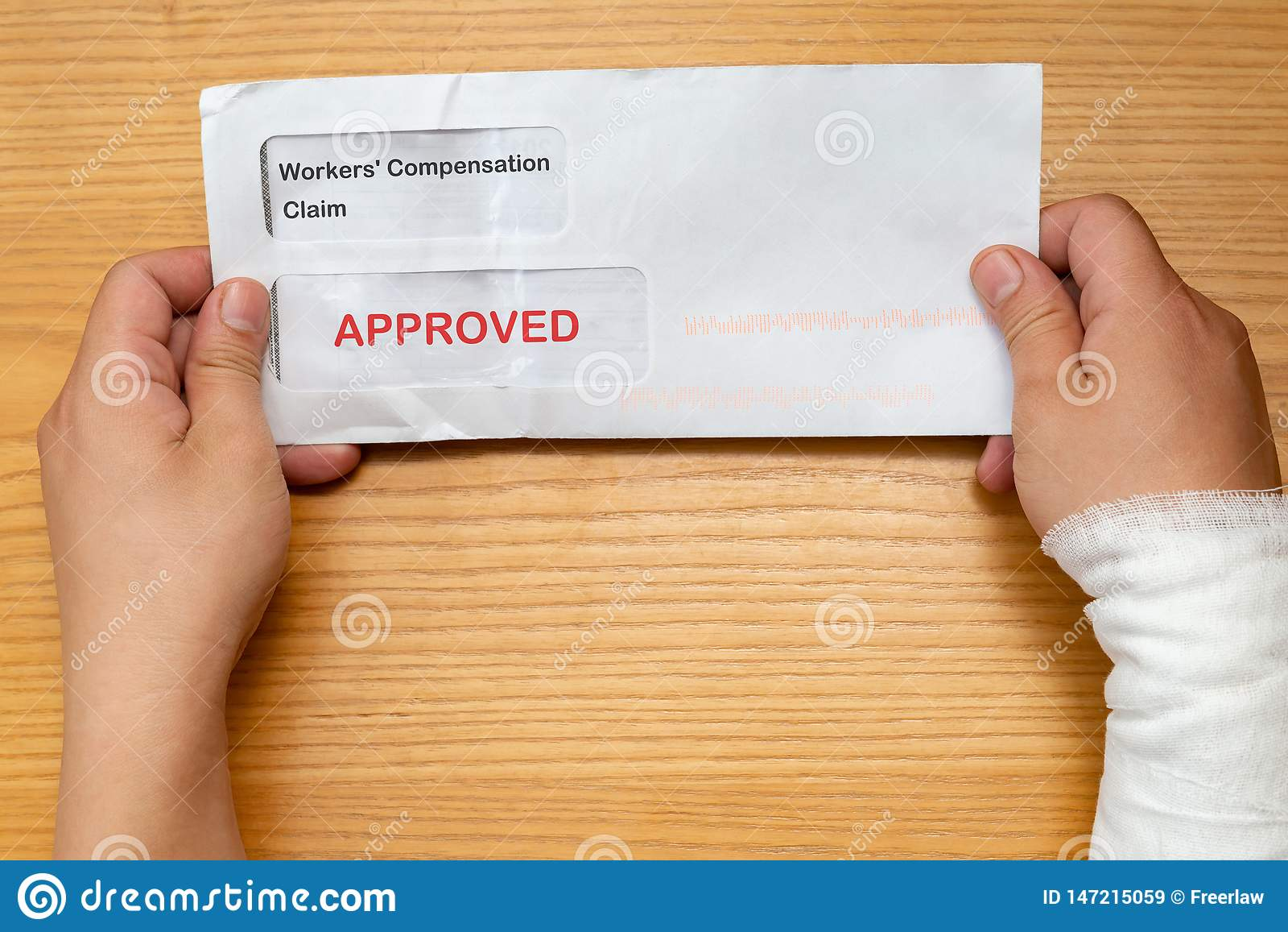 Wrapped hand holding envelope with workers compensation claim and result of approved removeable words with clipping path