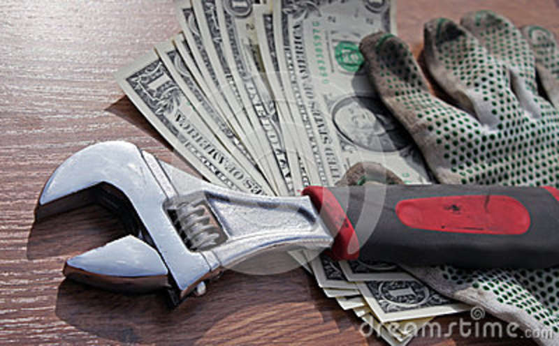 Wrench and gloves on dollars