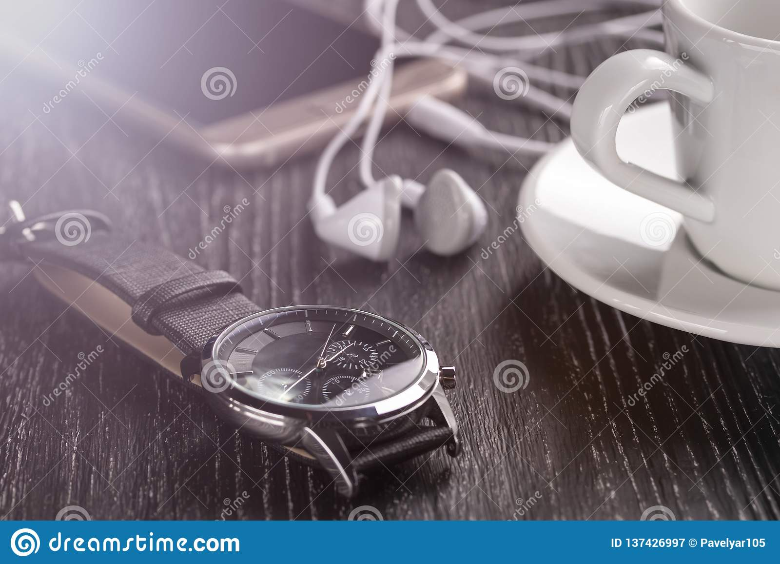 Wrist watch and mobile phone with headphones and a cup of coffee on a dark wooden table