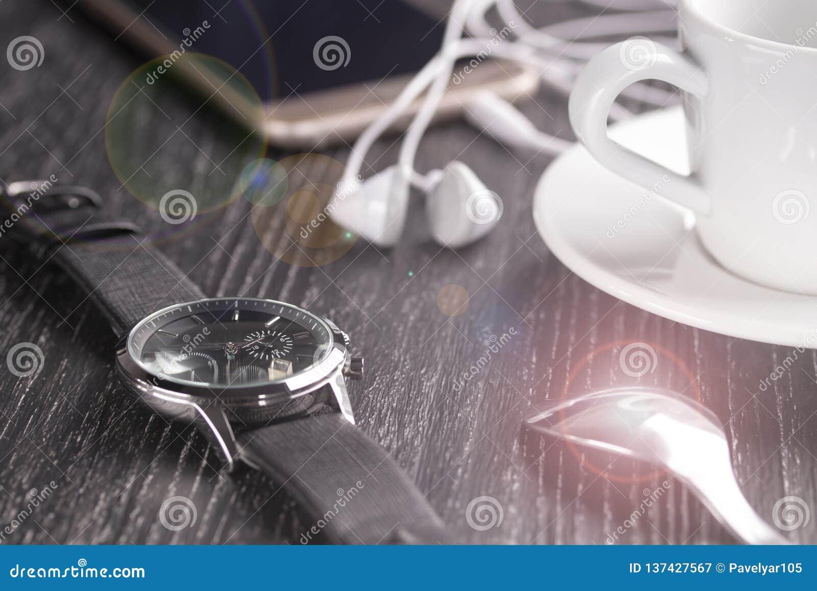 Wristwatch και κινητό τηλέφωνο με τα ακουστικά και ένα φλιτζάνι του καφέ σε έναν σκοτεινό ξύλινο πίνακα