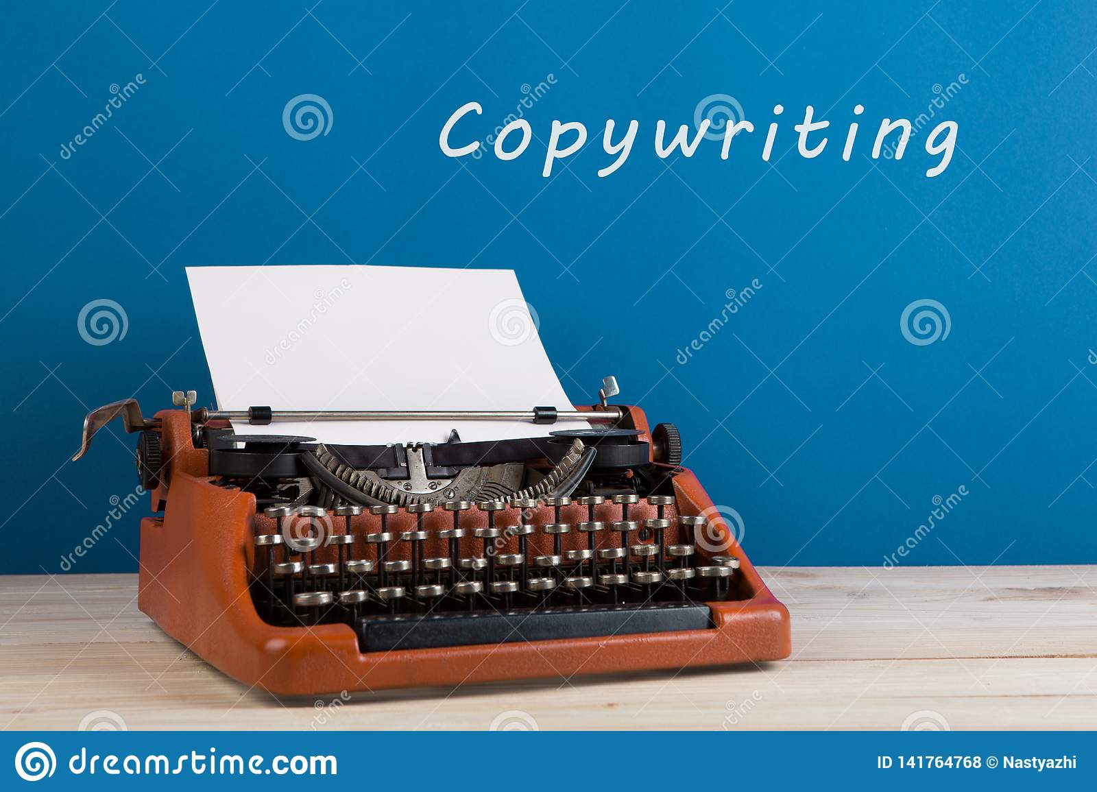 """writer's workplace - typewriter on blue blackboard background with text """"Copywriting"""