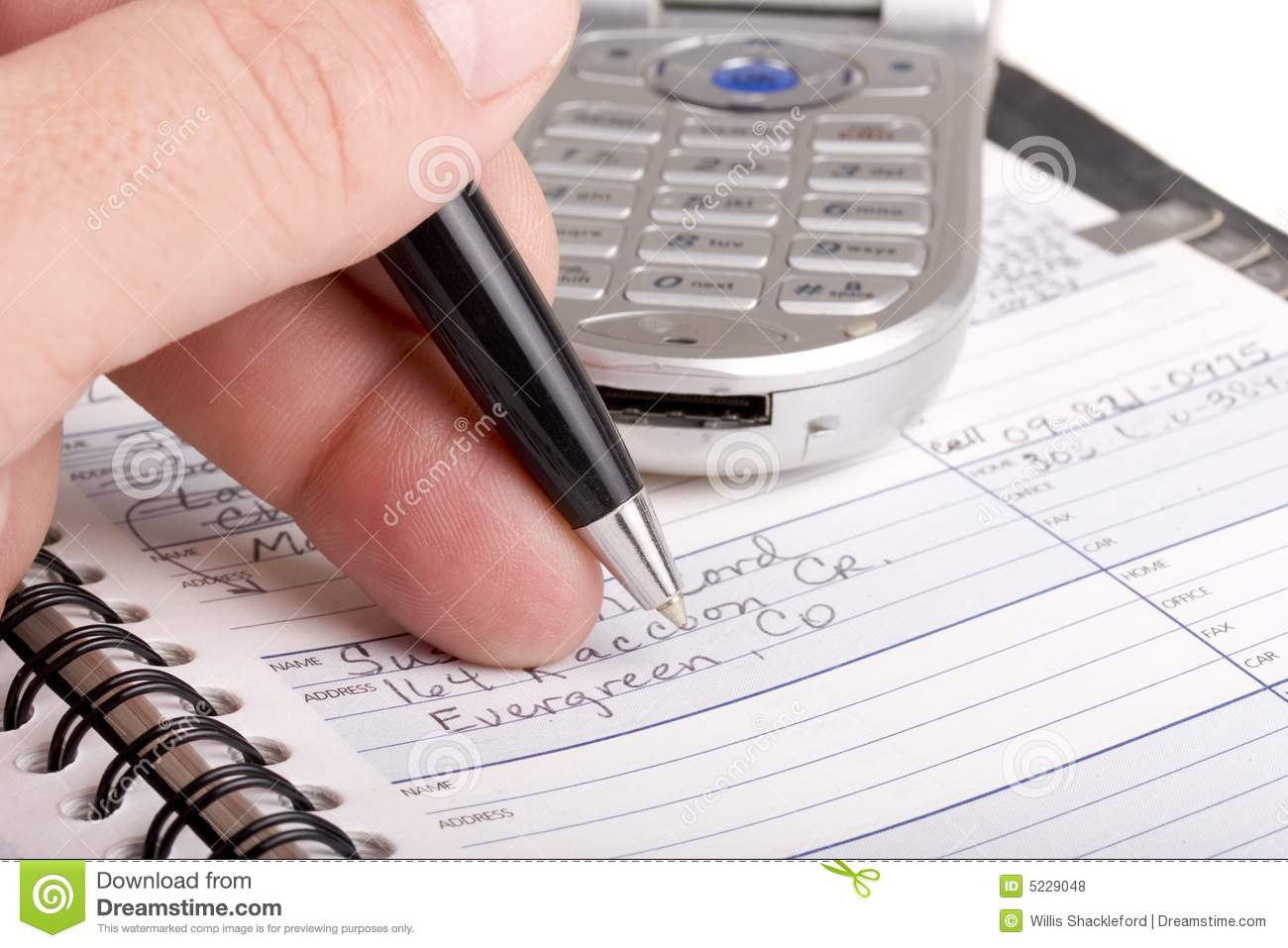 writing in address book with cell phone royalty free stock