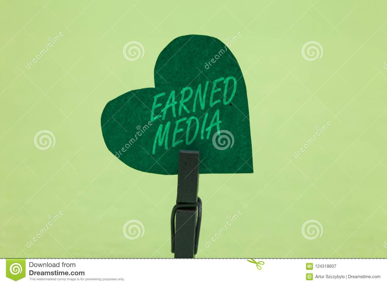 Writing note showing Earned Media. Business photo showcasing Publicity gained through promotional efforts by multimedia Clothespin
