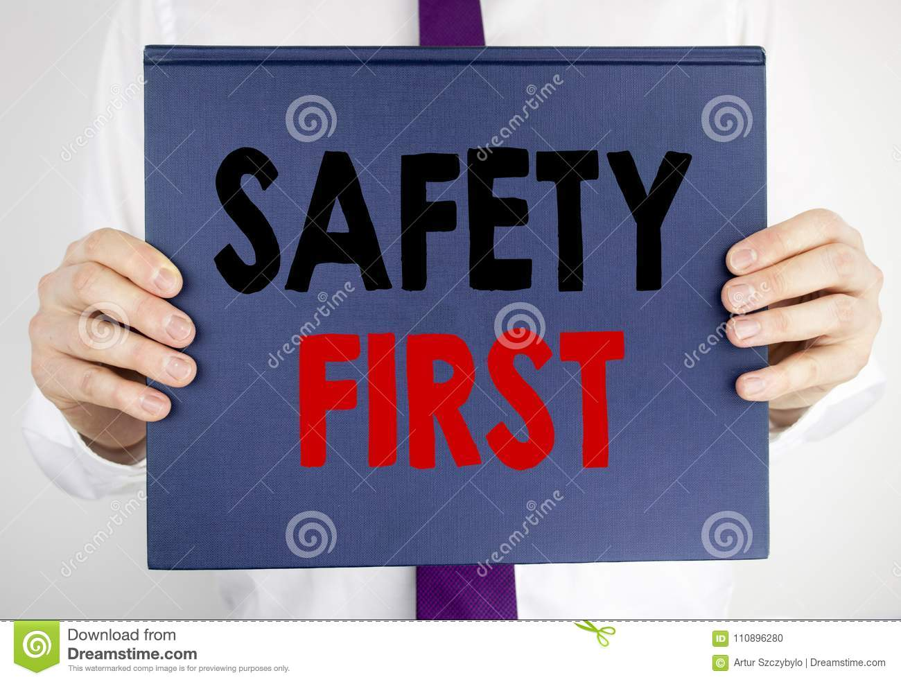 Writing text showing Safety First. Business concept for Safe Warning written on book notebook paper holding by the man in suit blu