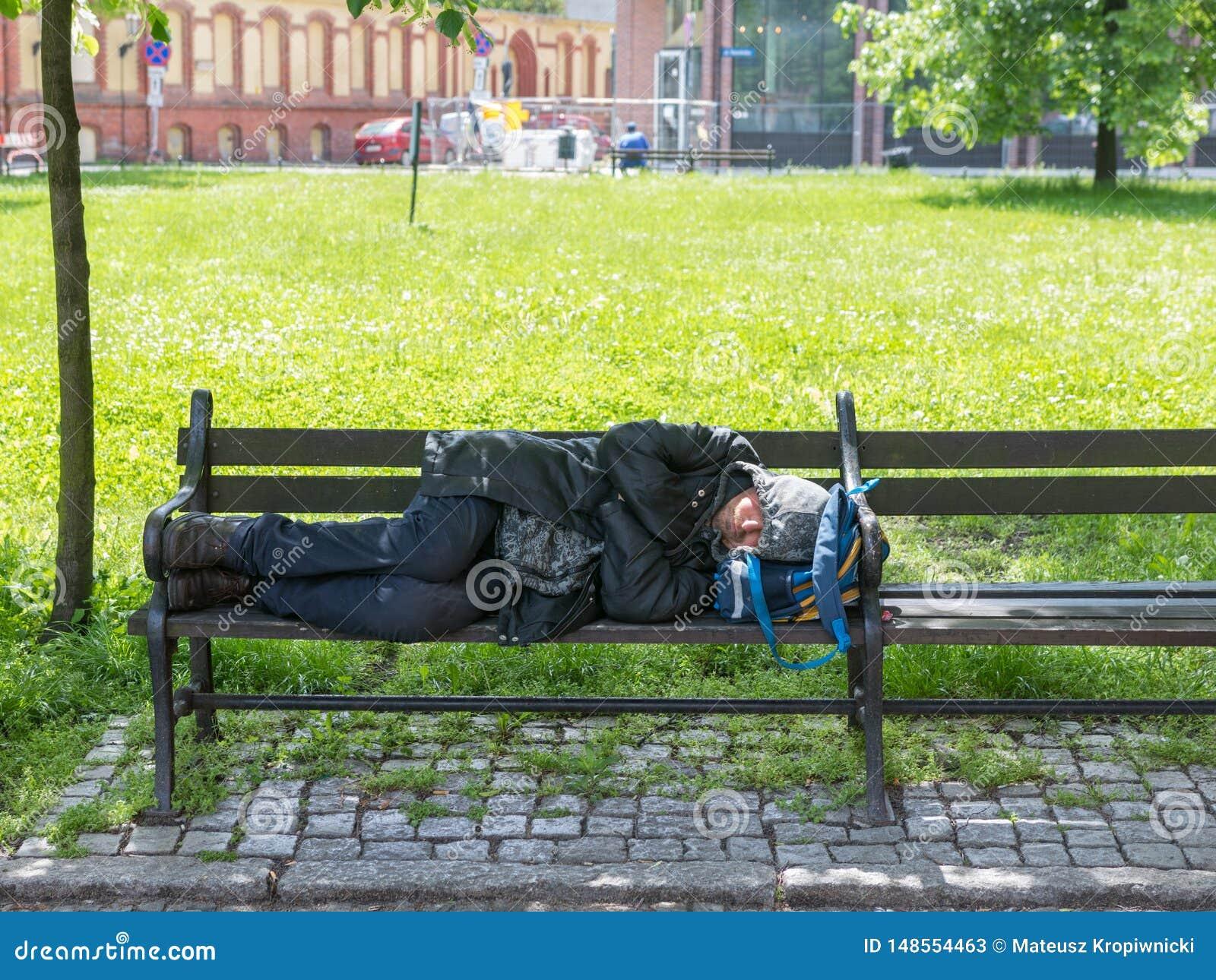 WrocÅ 'aw, Polen - Maj 24 2019: Den hemlösa mannen sover på en bänk nära ett nybyggt