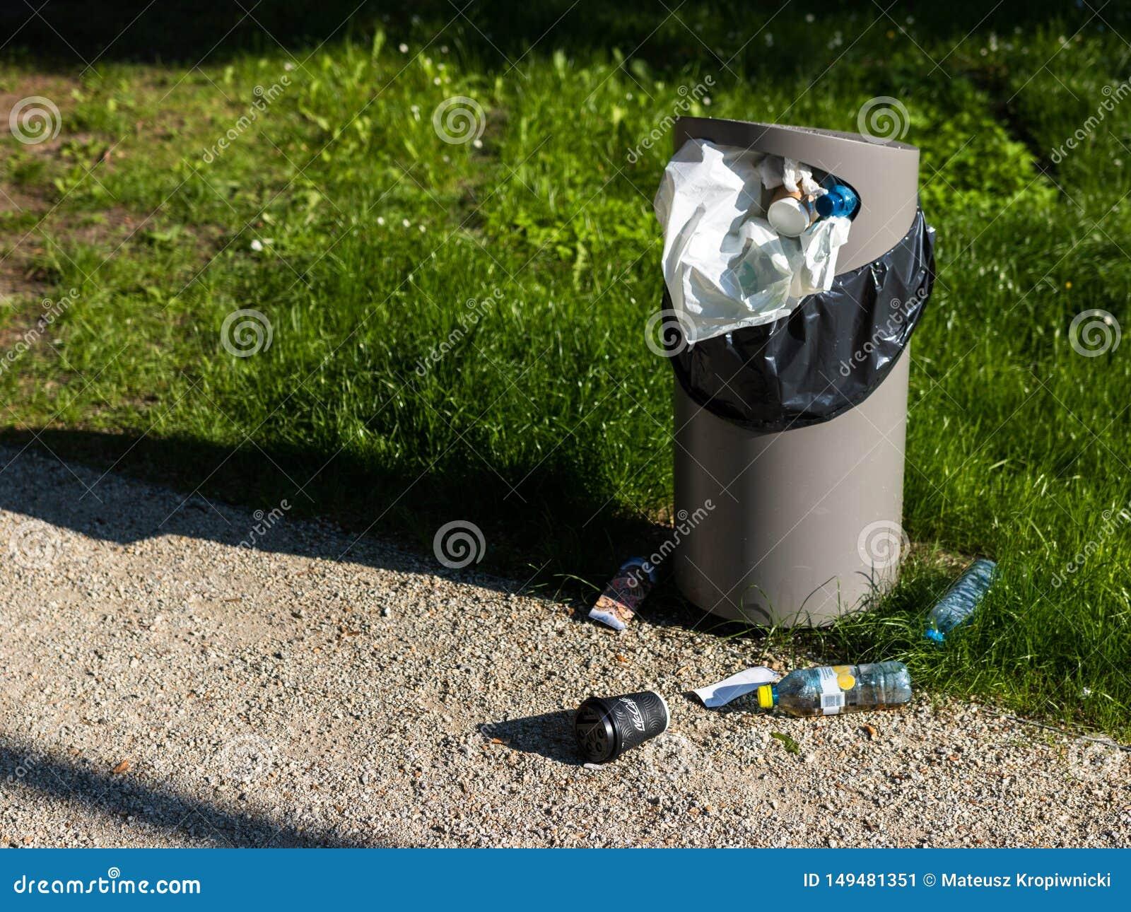 Wroclaw Polen - Juni 2 2019: En full soptunna Plast- avfalls sprids p? gr?set i allm?nheten parkerar bredvid japanskt