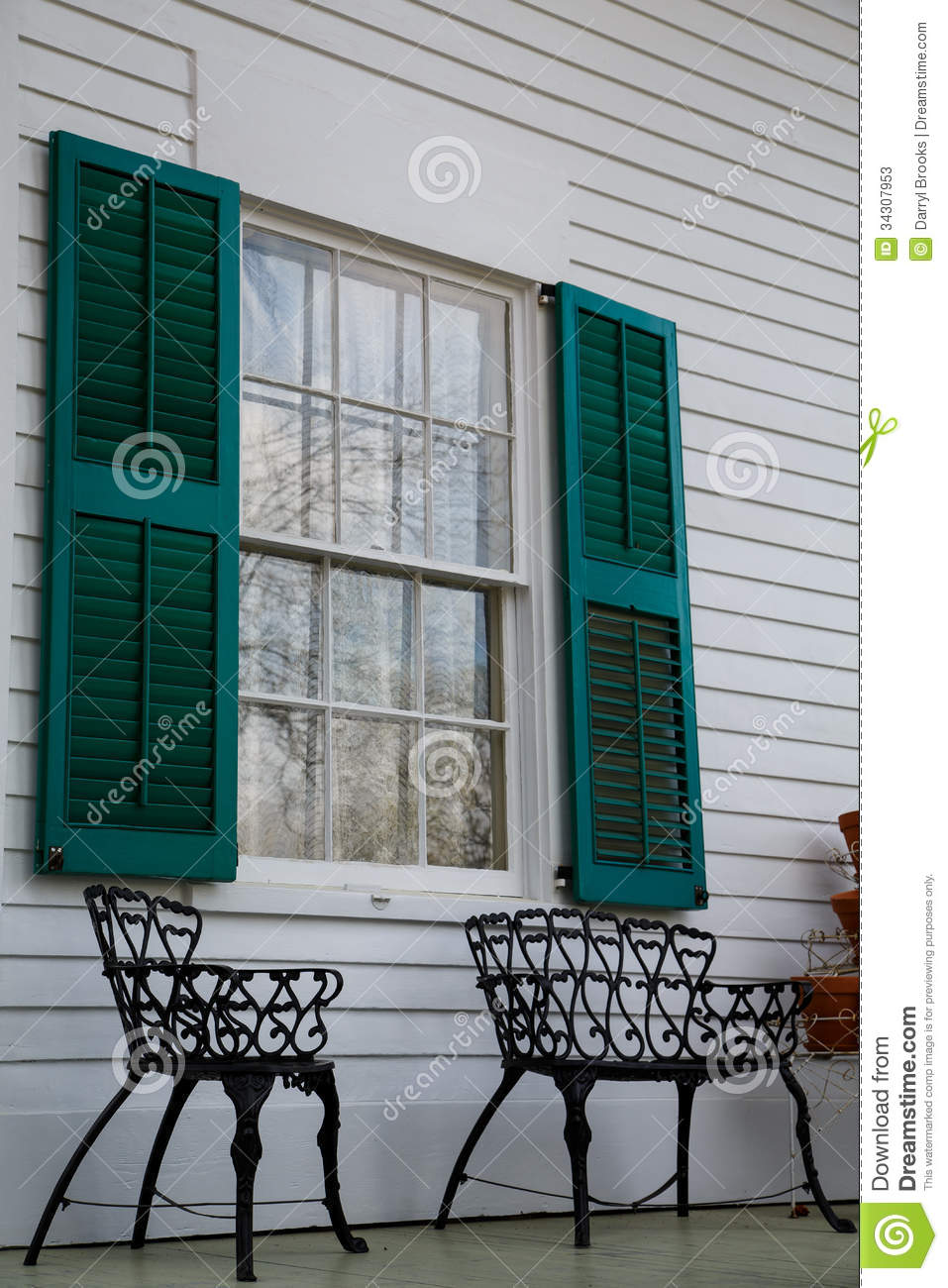 Wrought Iron Benches Under Green Shutters Stock Image