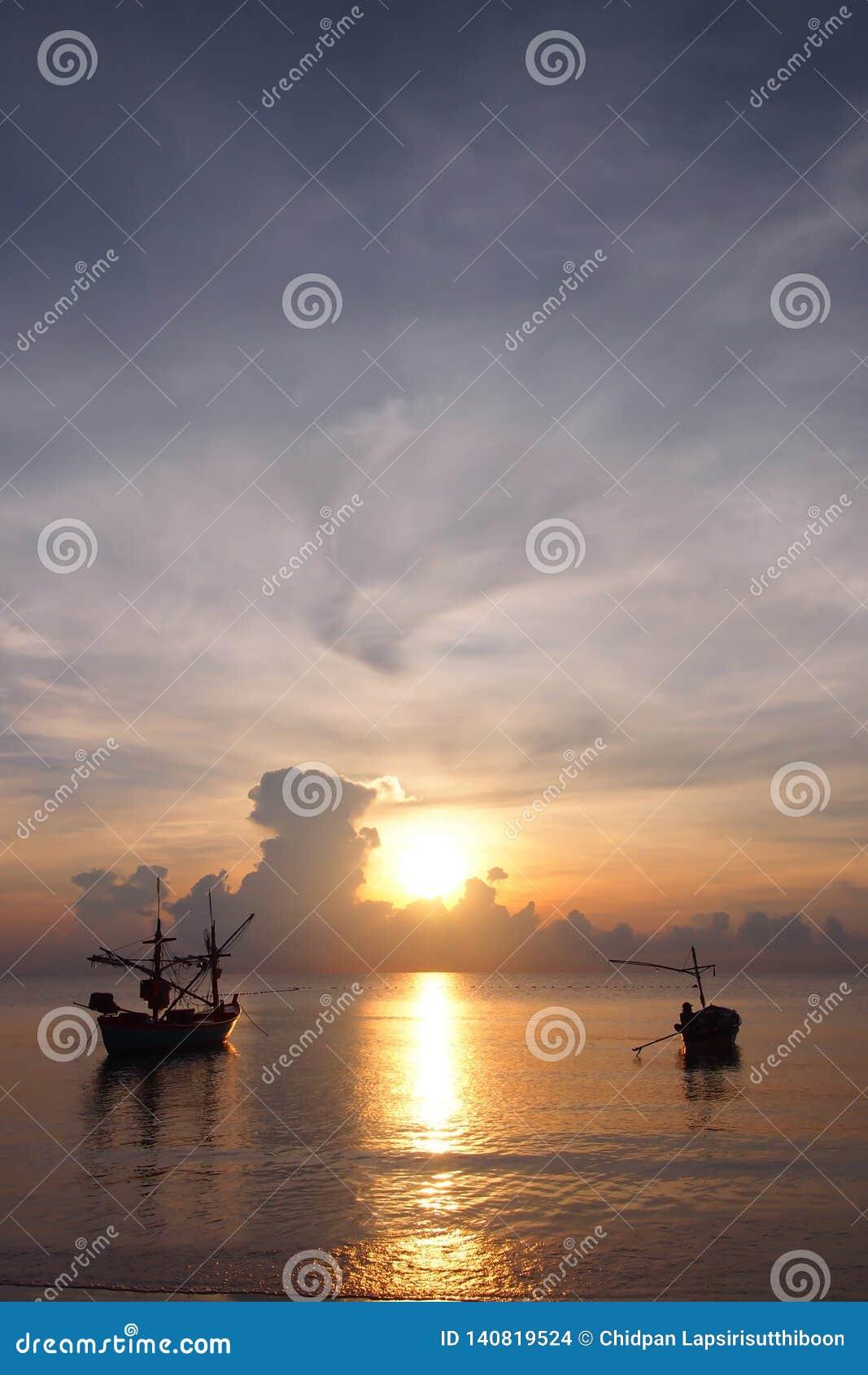Wschód słońca z rybakami przygotowywa łódź wychodzić ryba
