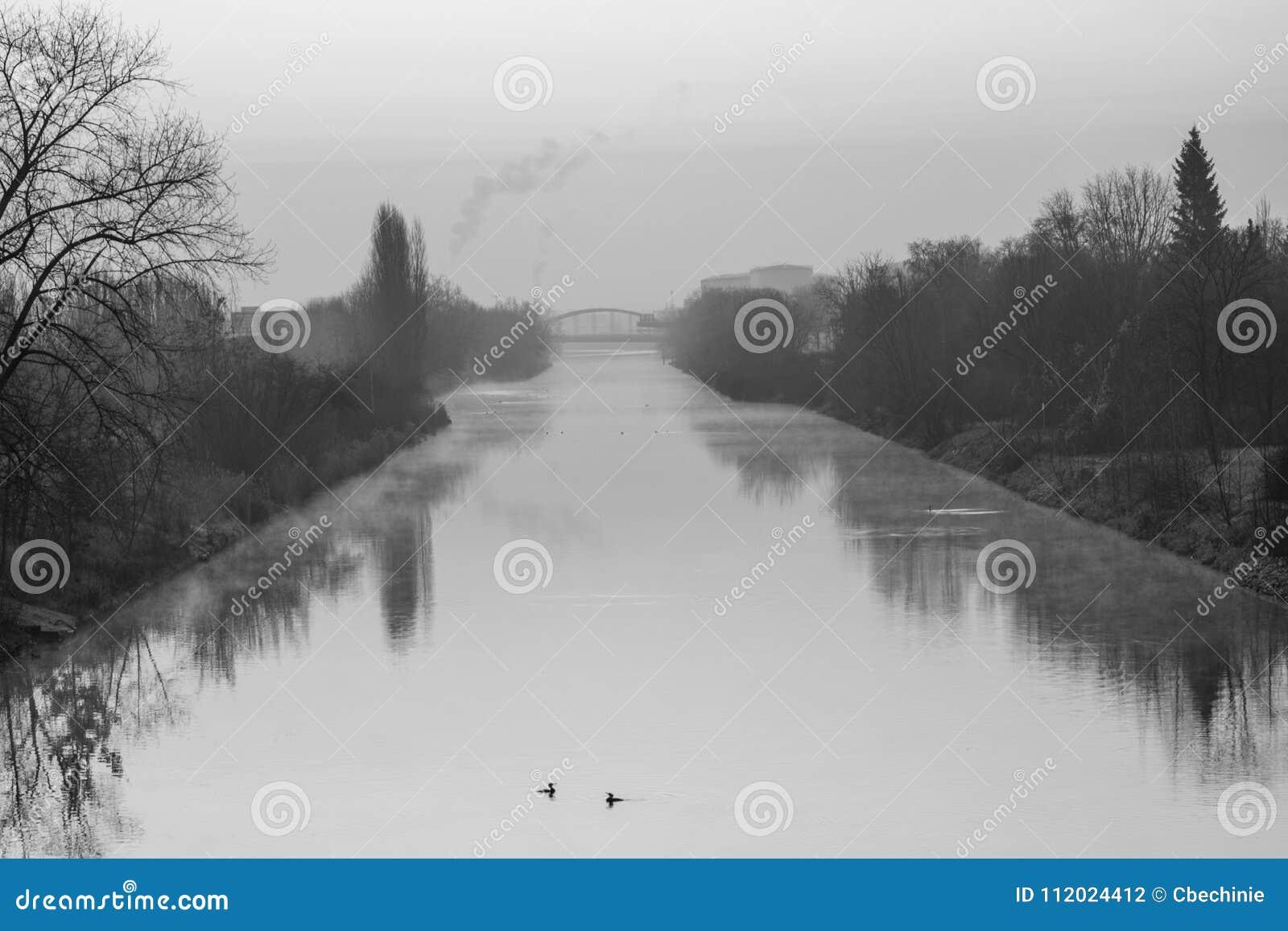 Wschód słońca nad drogą wodną w Berlin przy mglistym rankiem z widokiem most w tle - czarny i biały fotografia