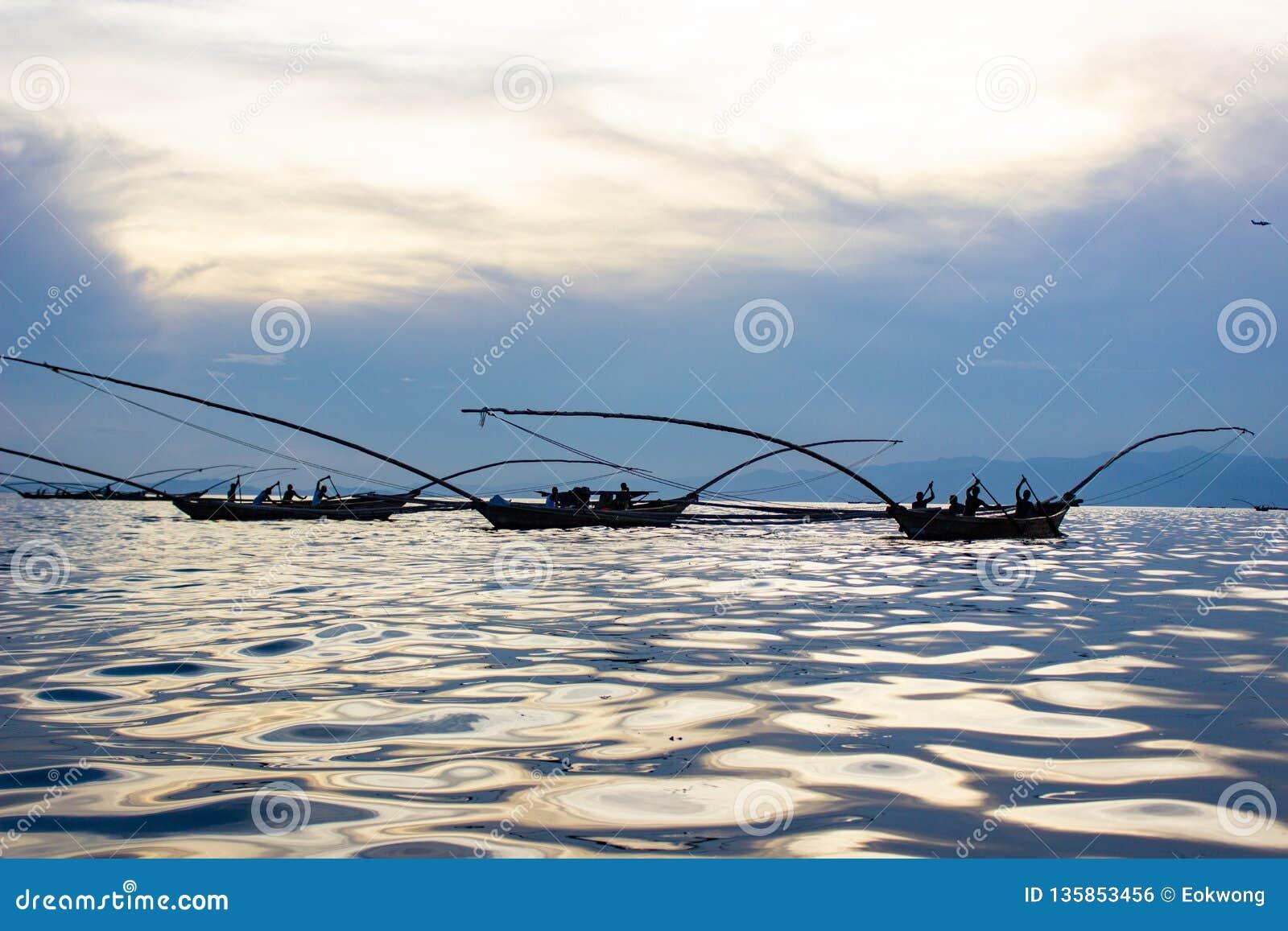 Wschodni Afrykańscy mężczyźni Łowi na jeziorze z słońca odbiciem na wodzie