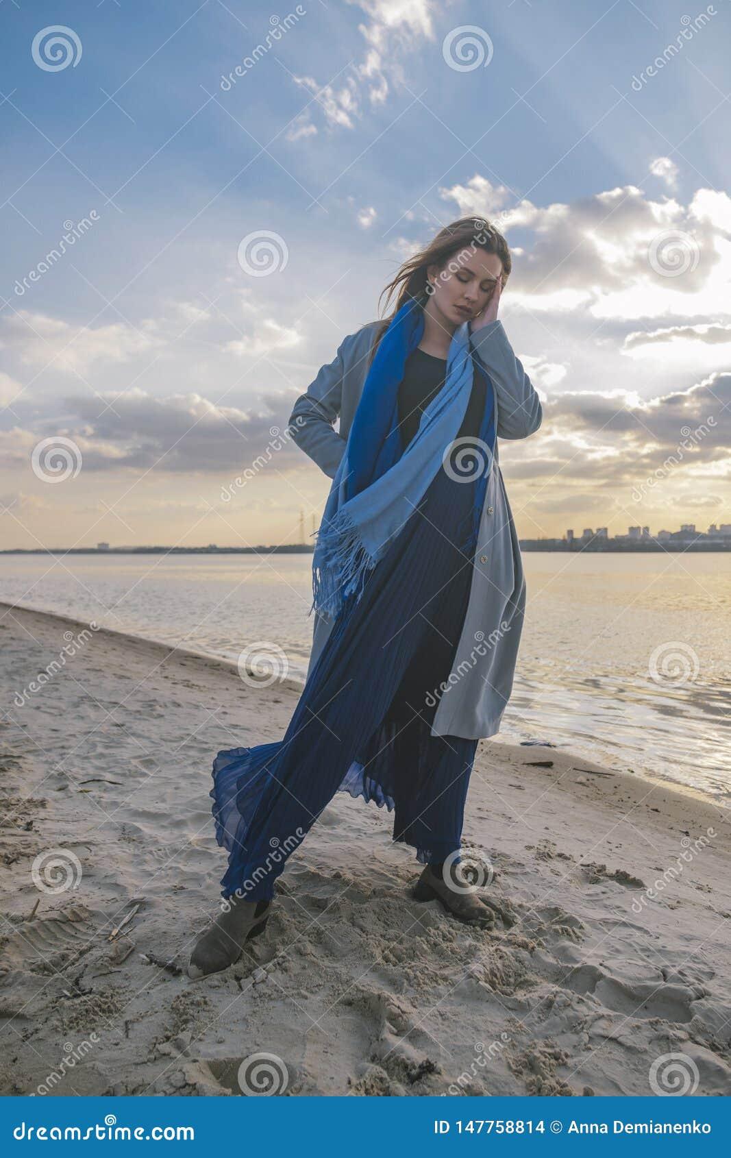 Wspaniała europejska kobieta w ciepłym żakiecie i sukni na spacerze w parkowej pobliskiej rzece wietrznie pogody Ona odzieżowa ko