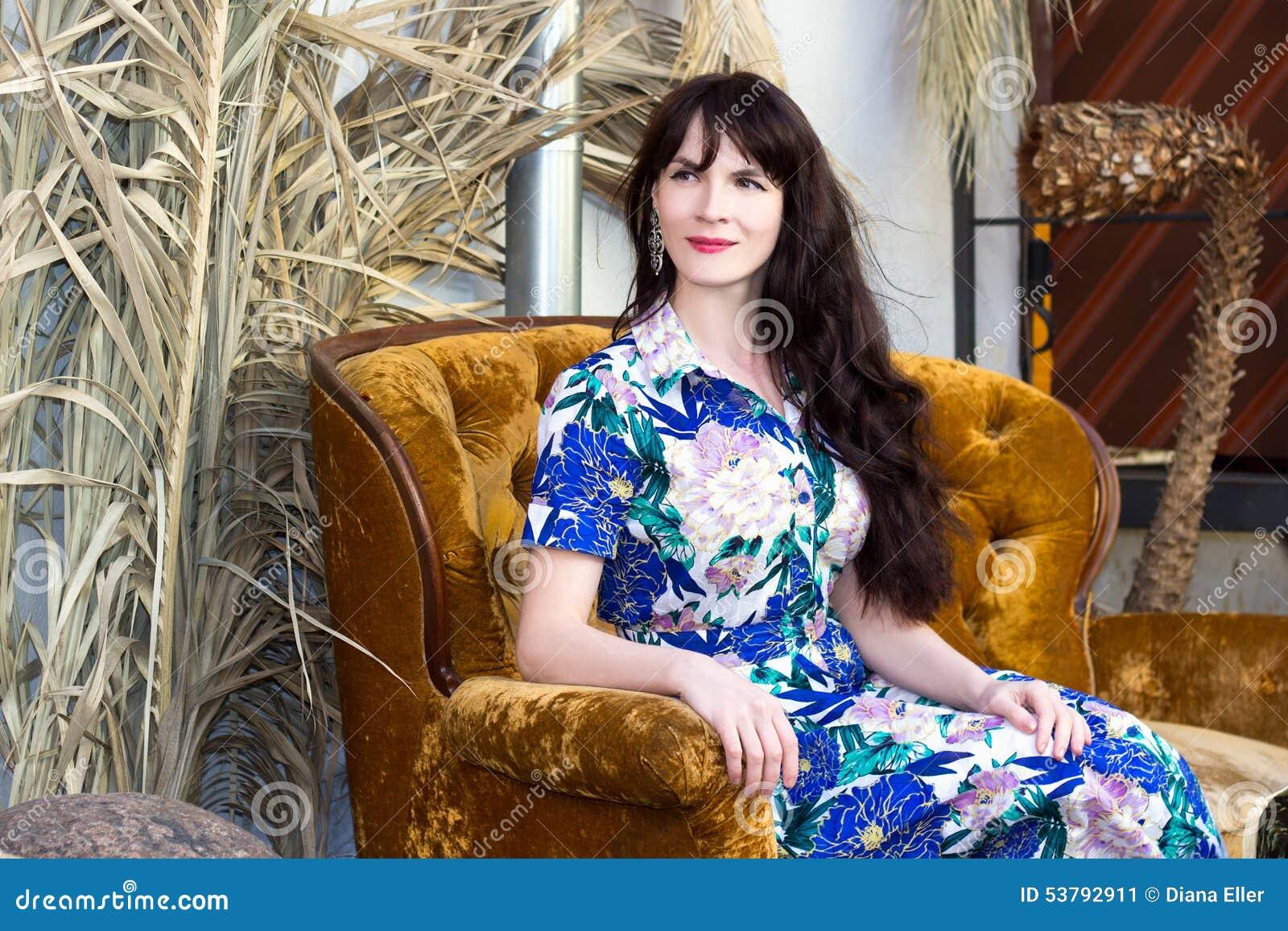 Wspaniała kobieta w błękit sukni obsiadaniu w lato kawiarni