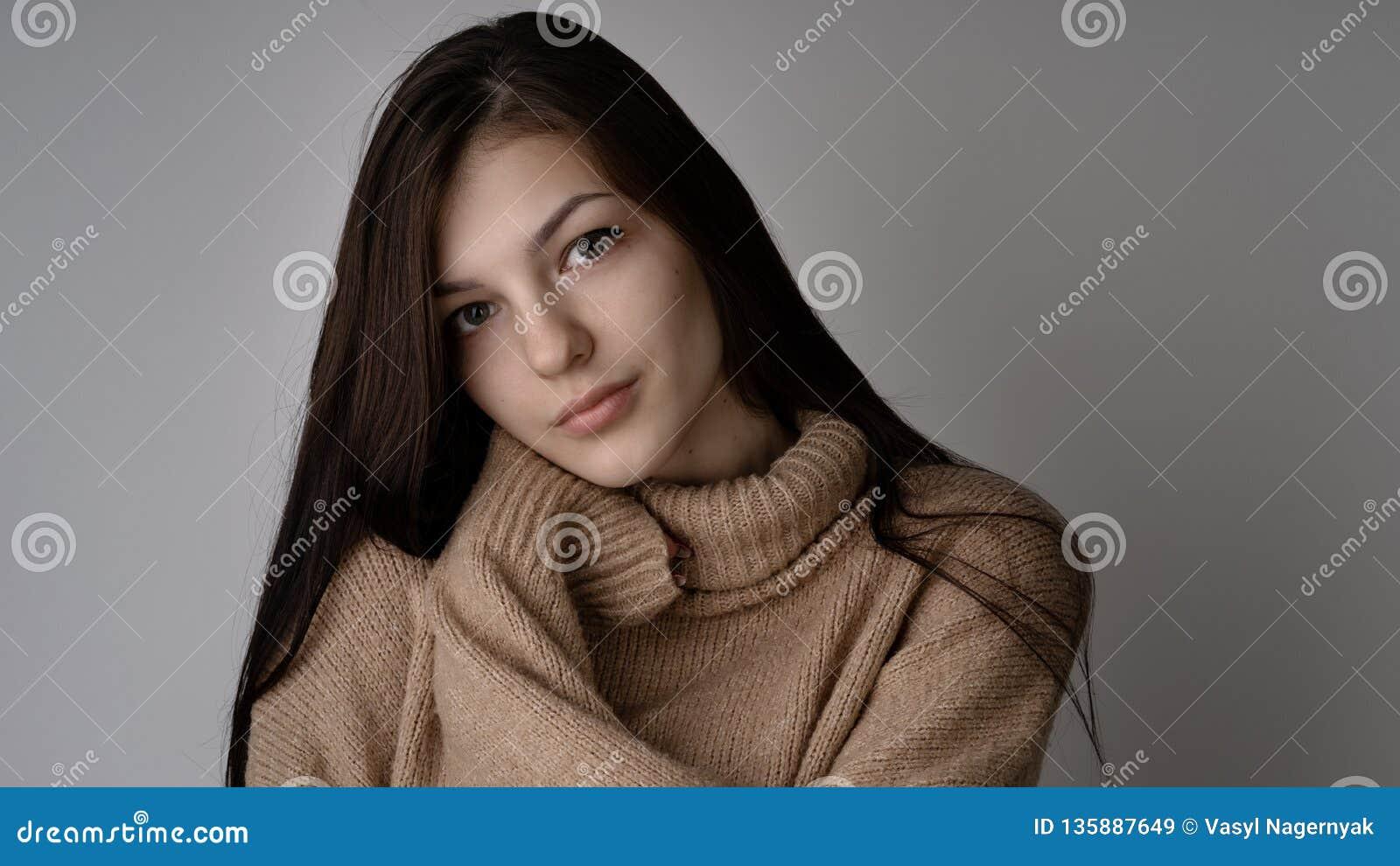 Wspaniała młoda brunetki kobieta w ciepłym trykotowym pulowerze na jasnopopielatym tle