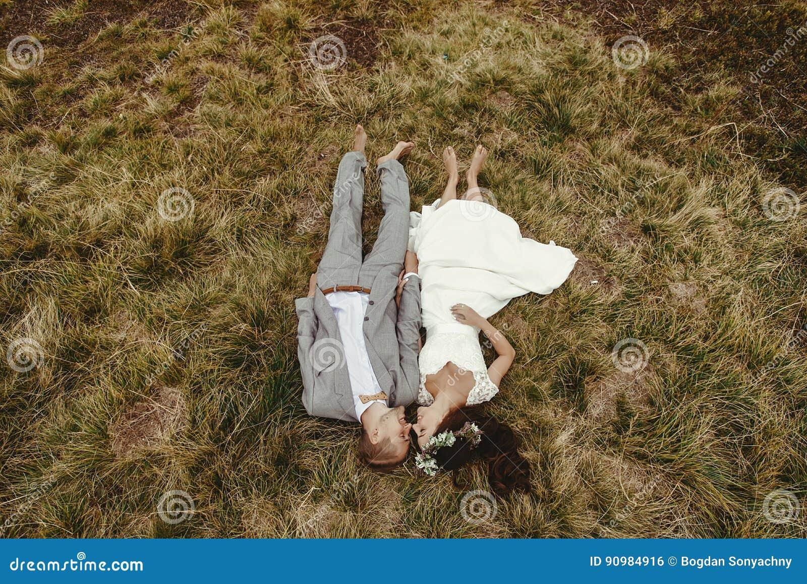 Wspaniała panna młoda i elegancki fornala lying on the beach na wierzchołku, boho ślubny cou
