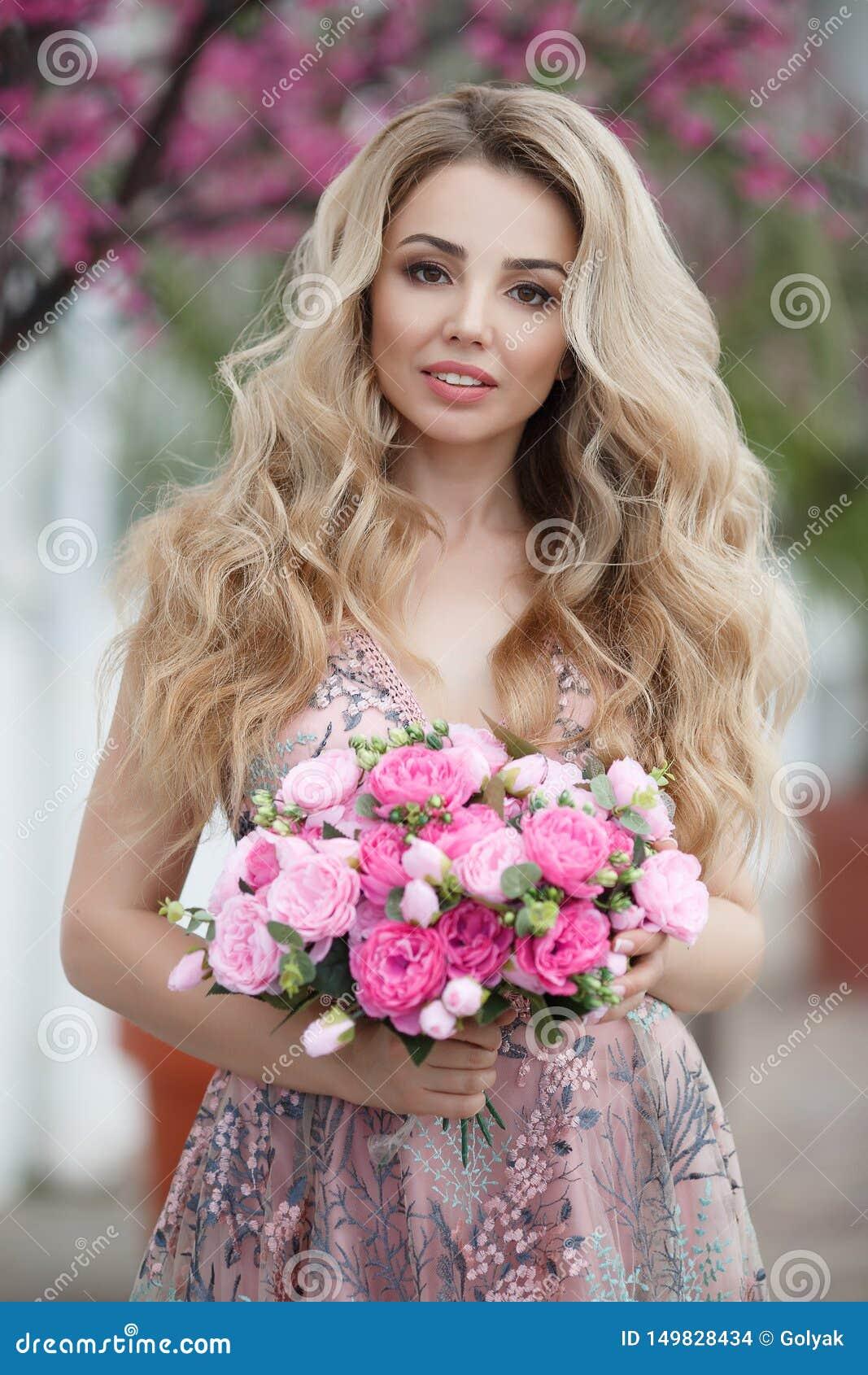 Wspaniały portret blondynki dziewczyna w wieczór seksownej menchii ubiera z bukietem piękne róże