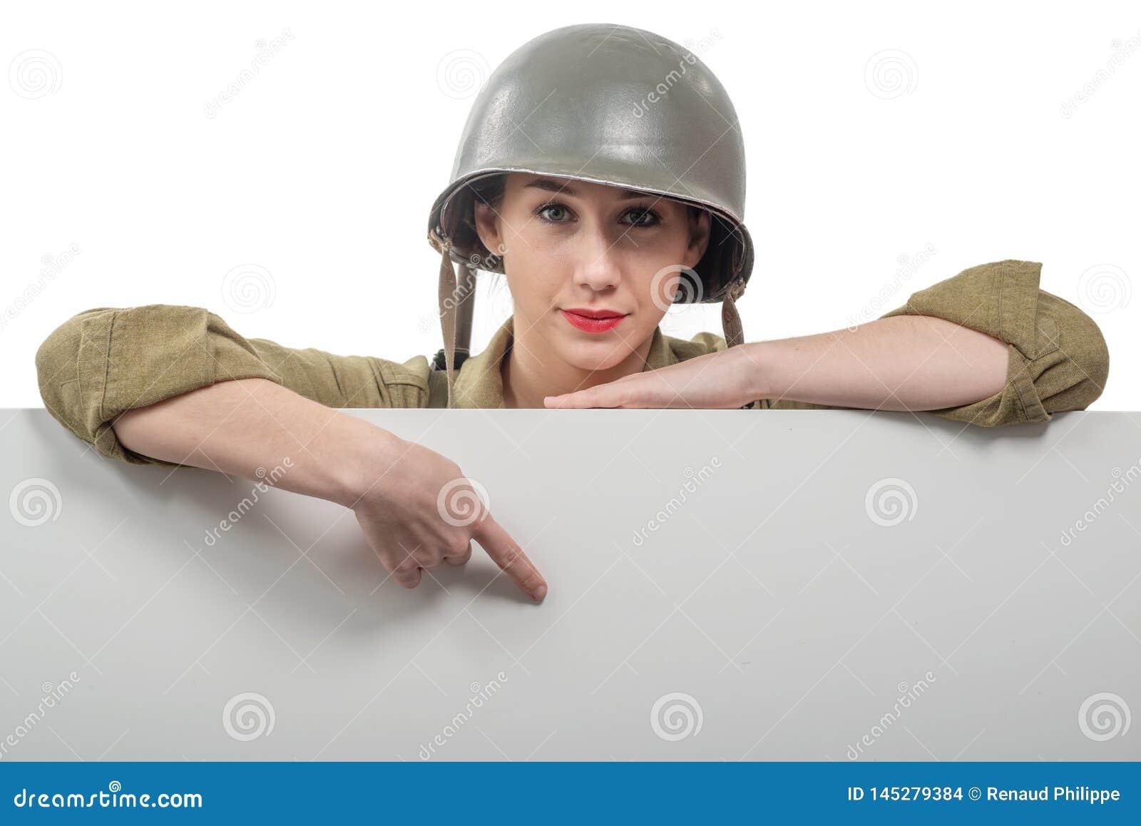 Η νέα γυναίκα έντυσε στην αμερικανική στρατιωτική στολή ww2 που παρουσιάζει κενή κενή πινακίδα