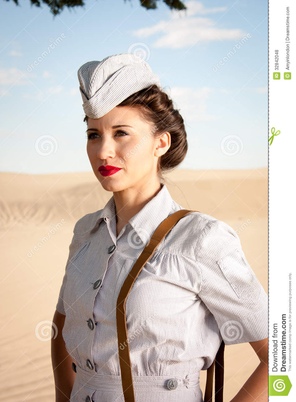 beautiful young WWII nurse, in authentic uniform, stares off into ...