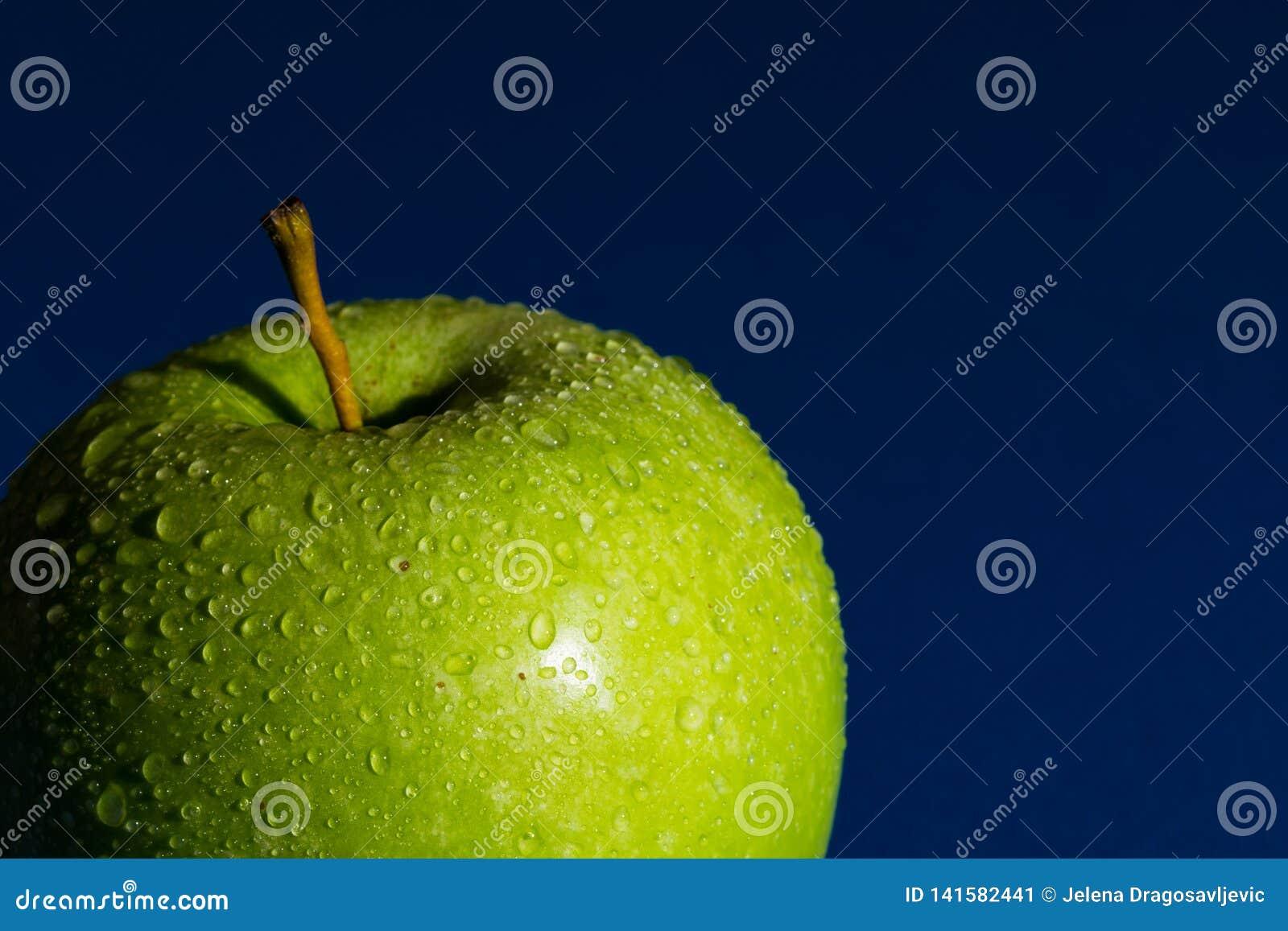 Wyśmienicie zielony jabłko z perłami wodny i błękitny tło