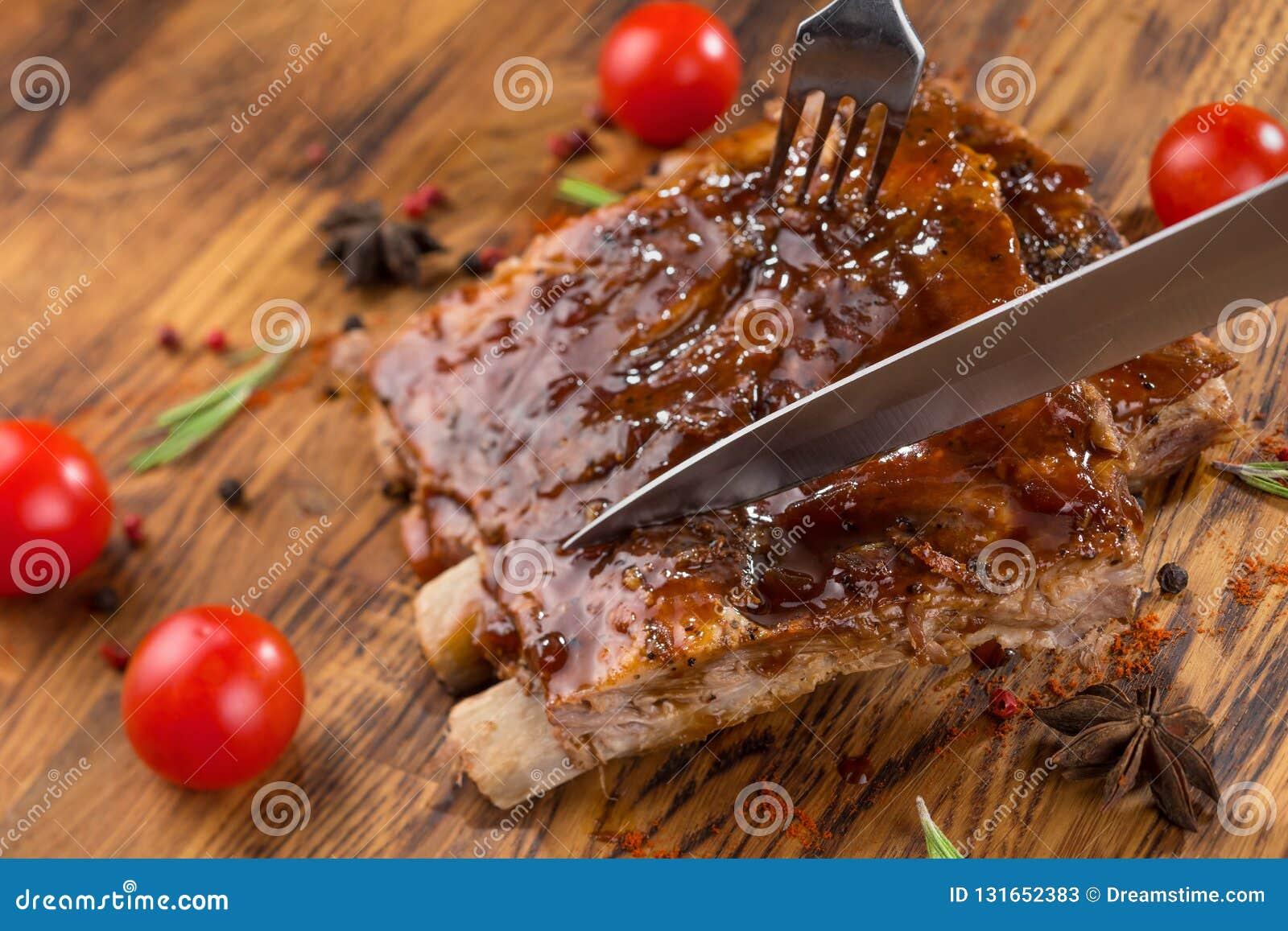 Wyśmienicie barbecued ziobro przyprawiający z korzennym fastrygowanie kumberlandem na starym nieociosanym drewnianym zakupy wsiad