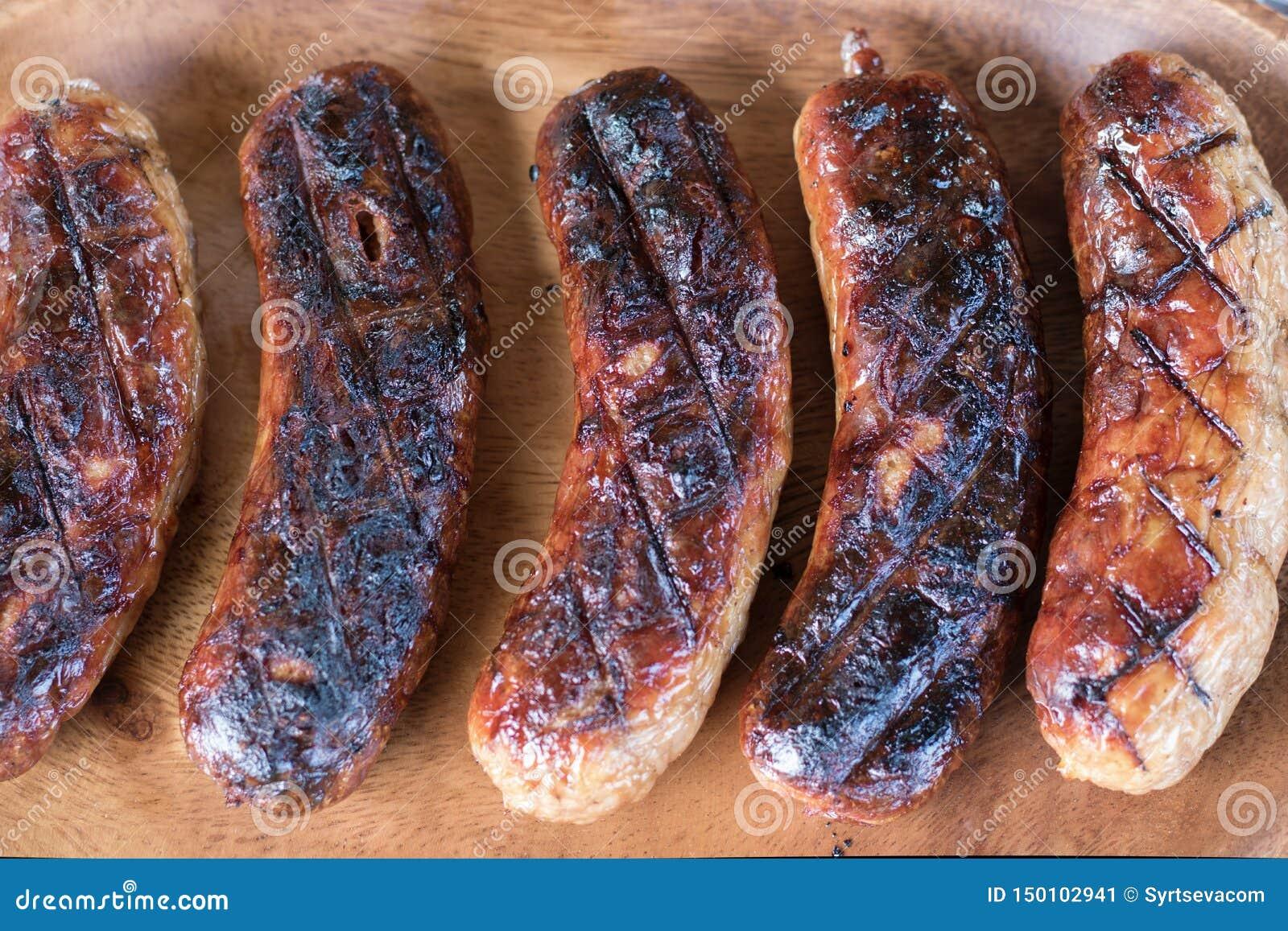 Wyśmienicie mięsne kiełbasy piec na grillu na drewnianym półkowym tle