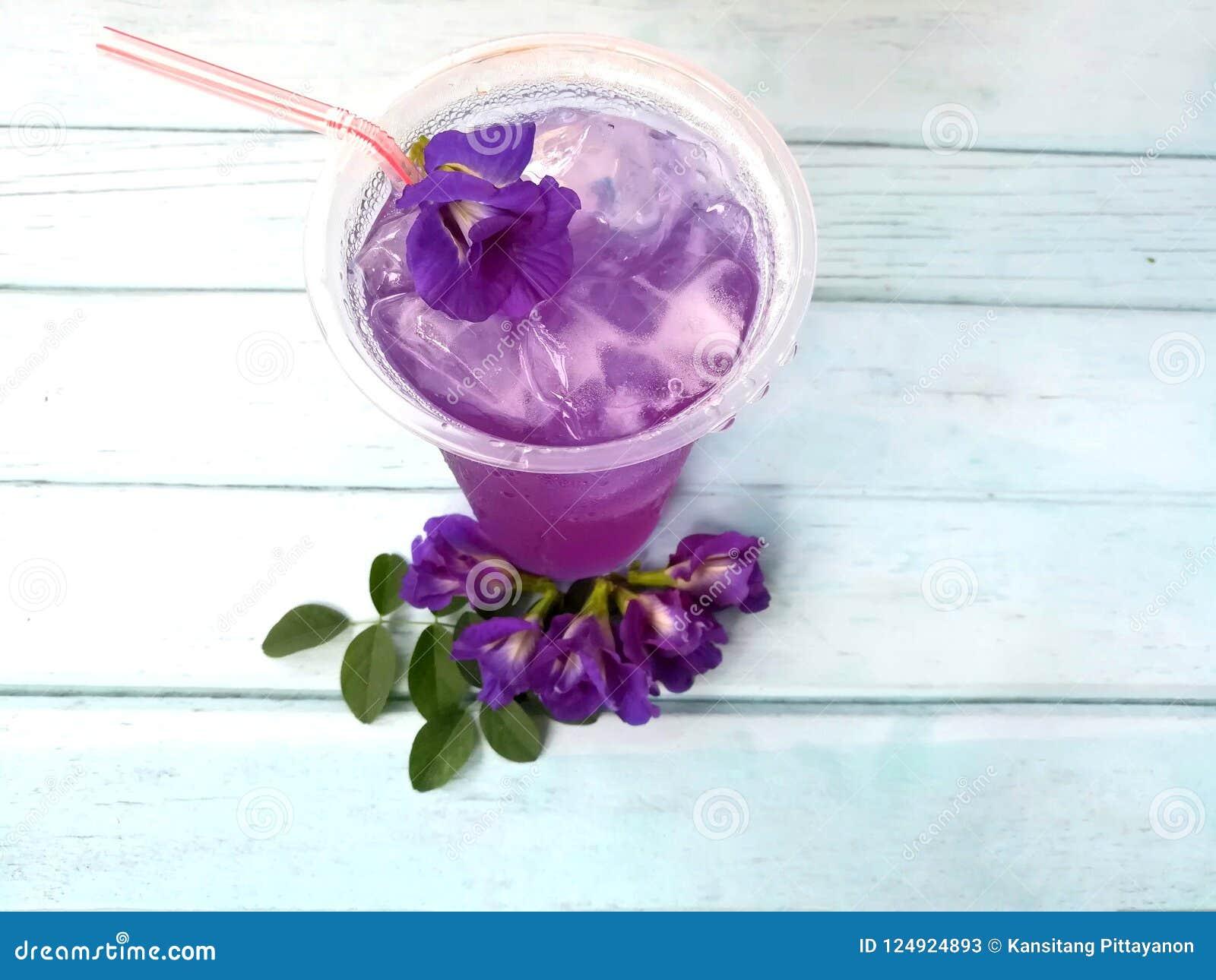 Wyśmienicie motyliego grochu dink zimno, anchan kwiat, błękitny drewniany stół
