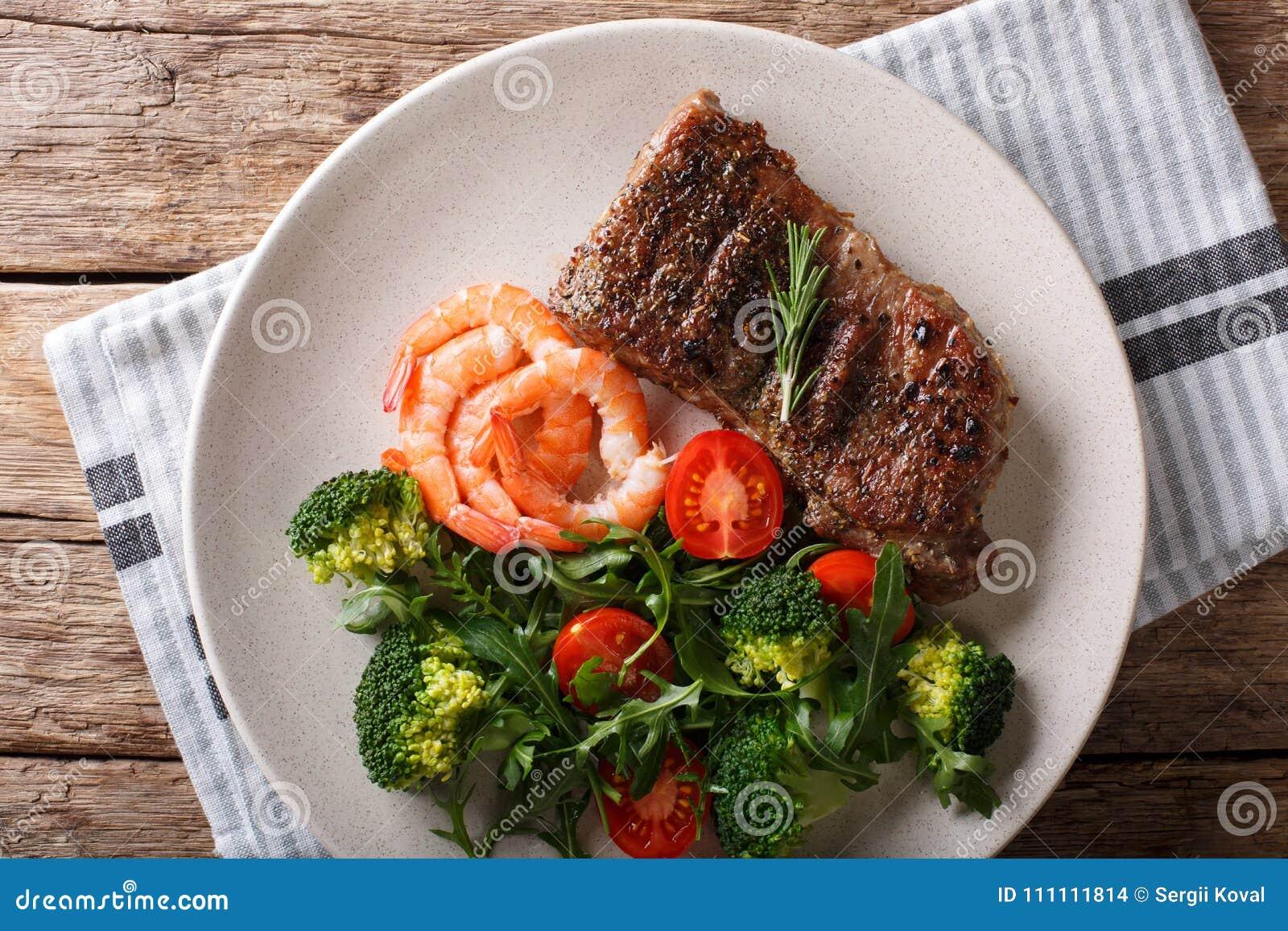 Wyśmienicie piec na grillu wołowina stek z krewetkami i brokułami, pomidory,