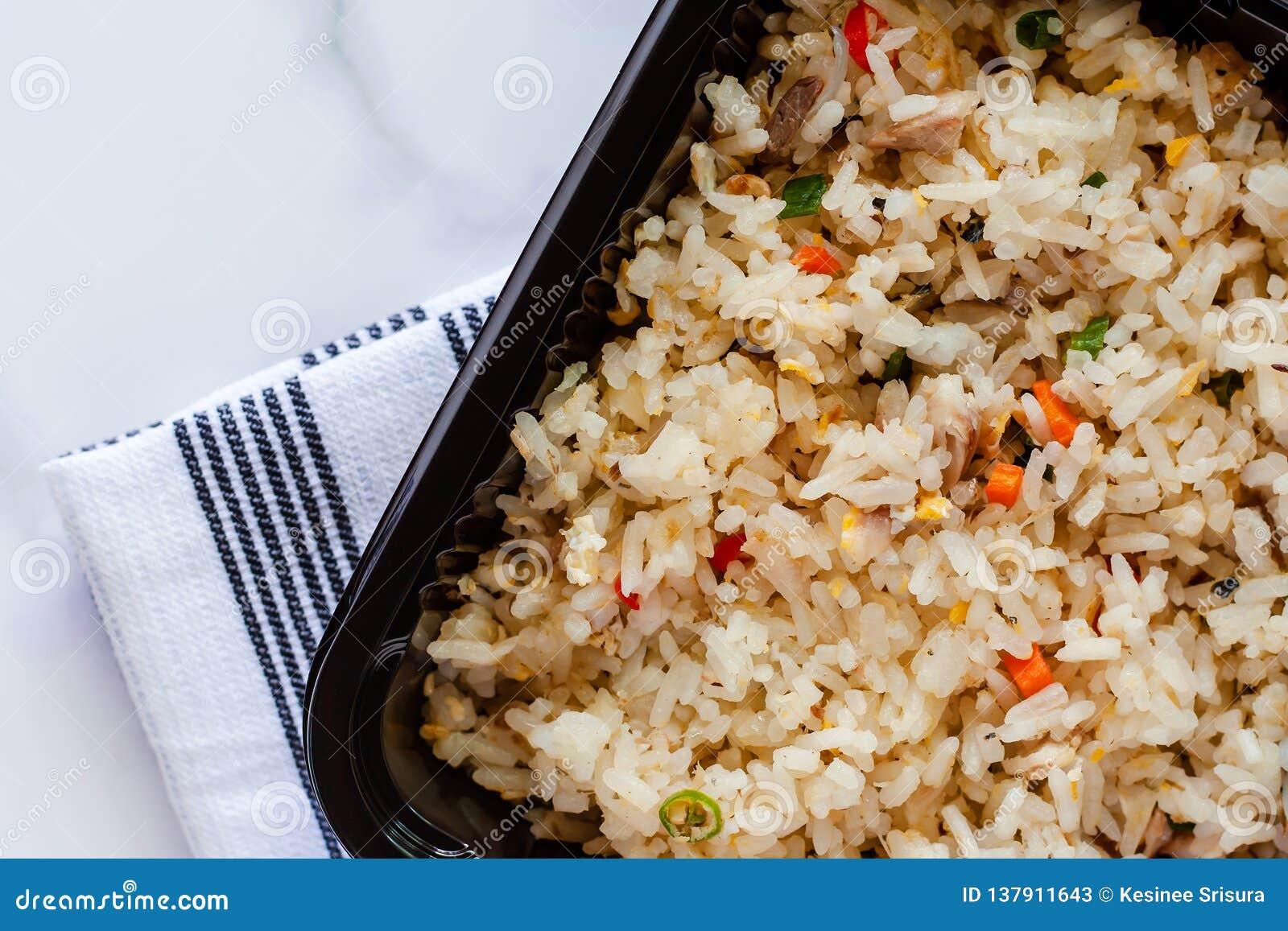 Wyśmienicie smażący ryż w lunchu pudełku z napery na marmurowym tle