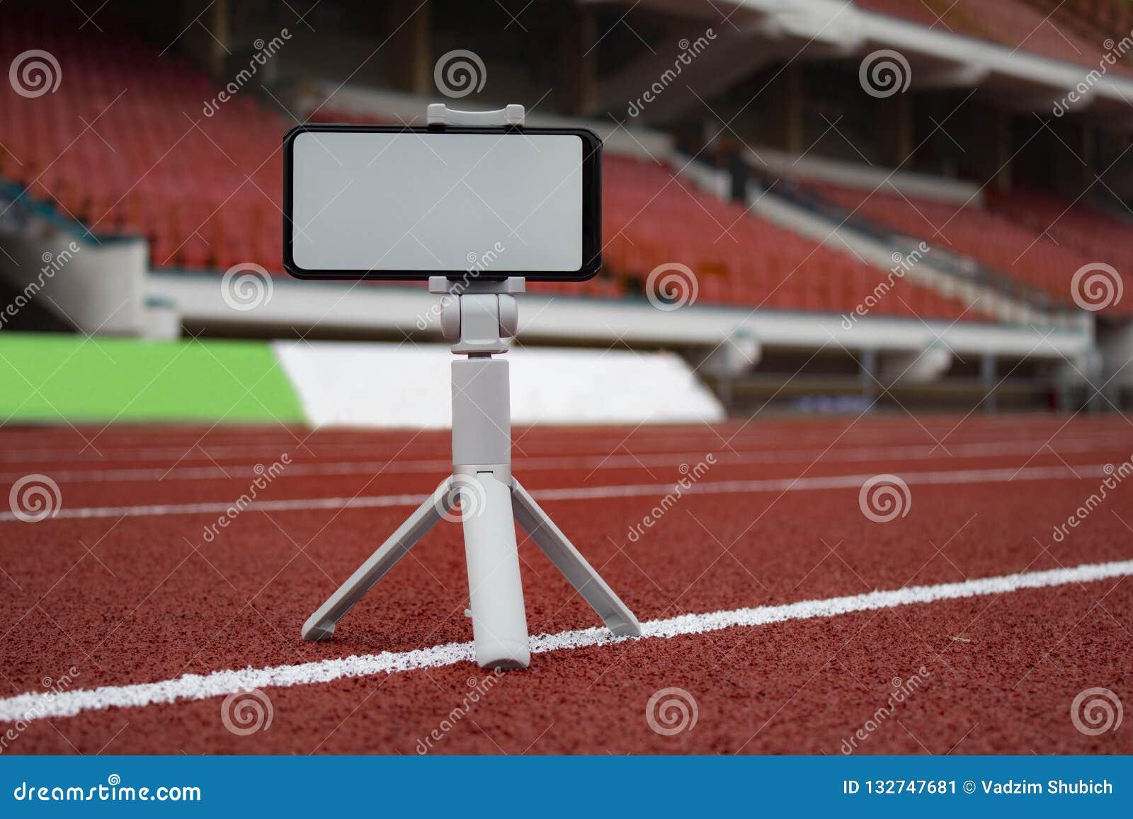 Wyśmiewa w górę czarnego smartphone z tripod Bielu ekran dla projekta szablonu na tle czerwony ślad dla