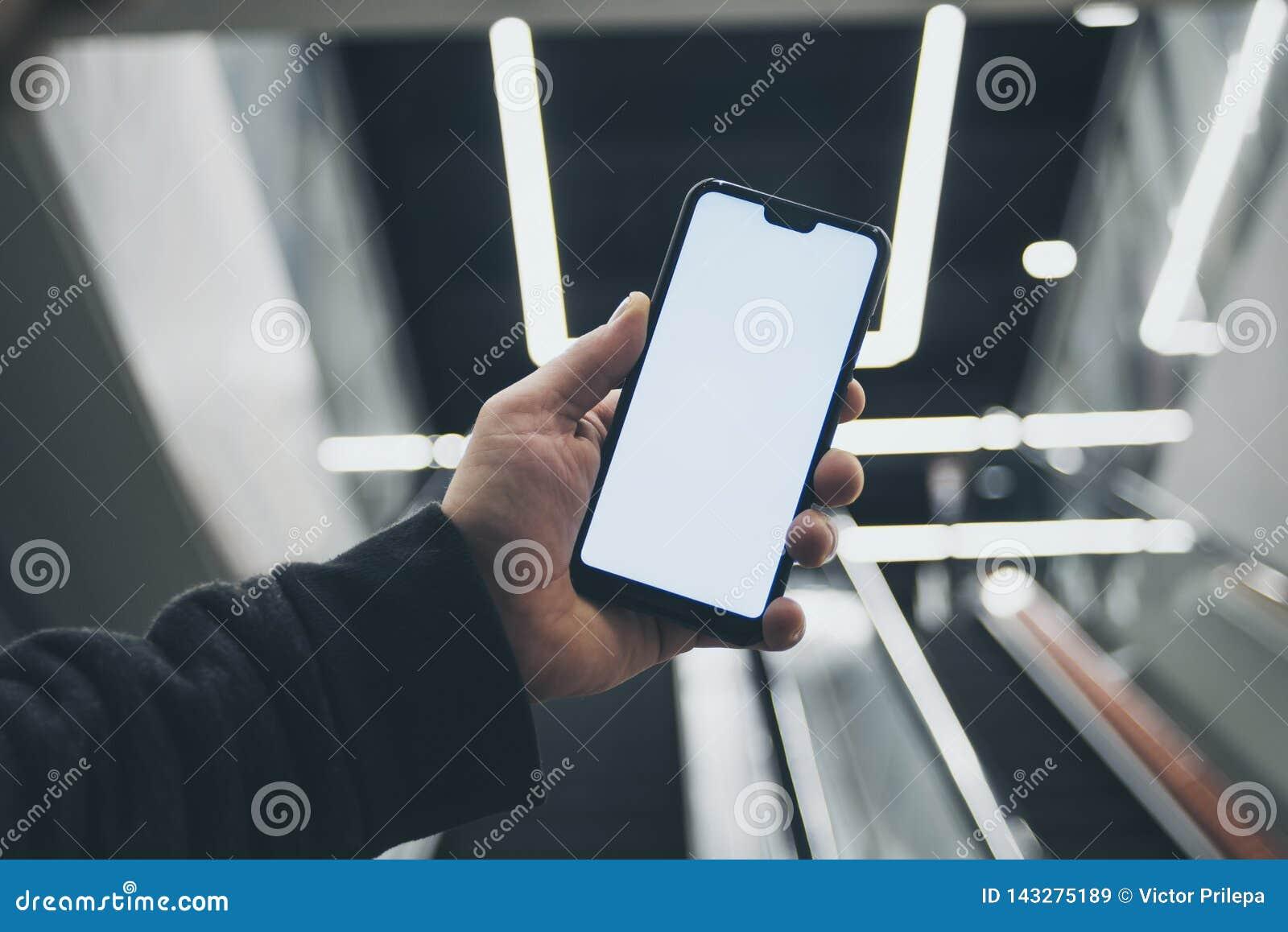 Wyśmiewa w górę smartphone w ręce, na tle eskalator w świecących lampach i centrum handlowym