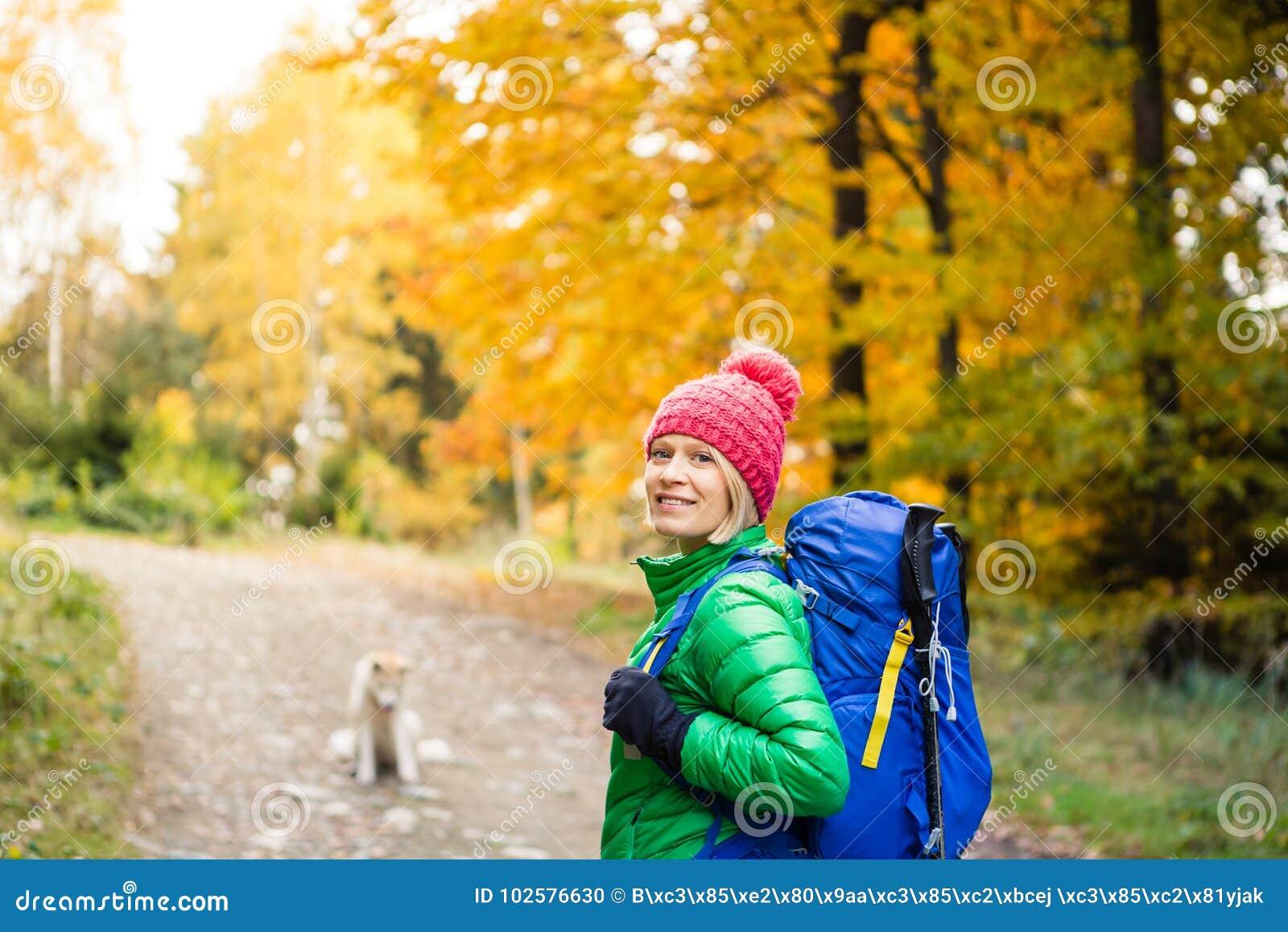 Wycieczkować kobiety patrzeje inspiracyjnego jesieni golde z plecakiem
