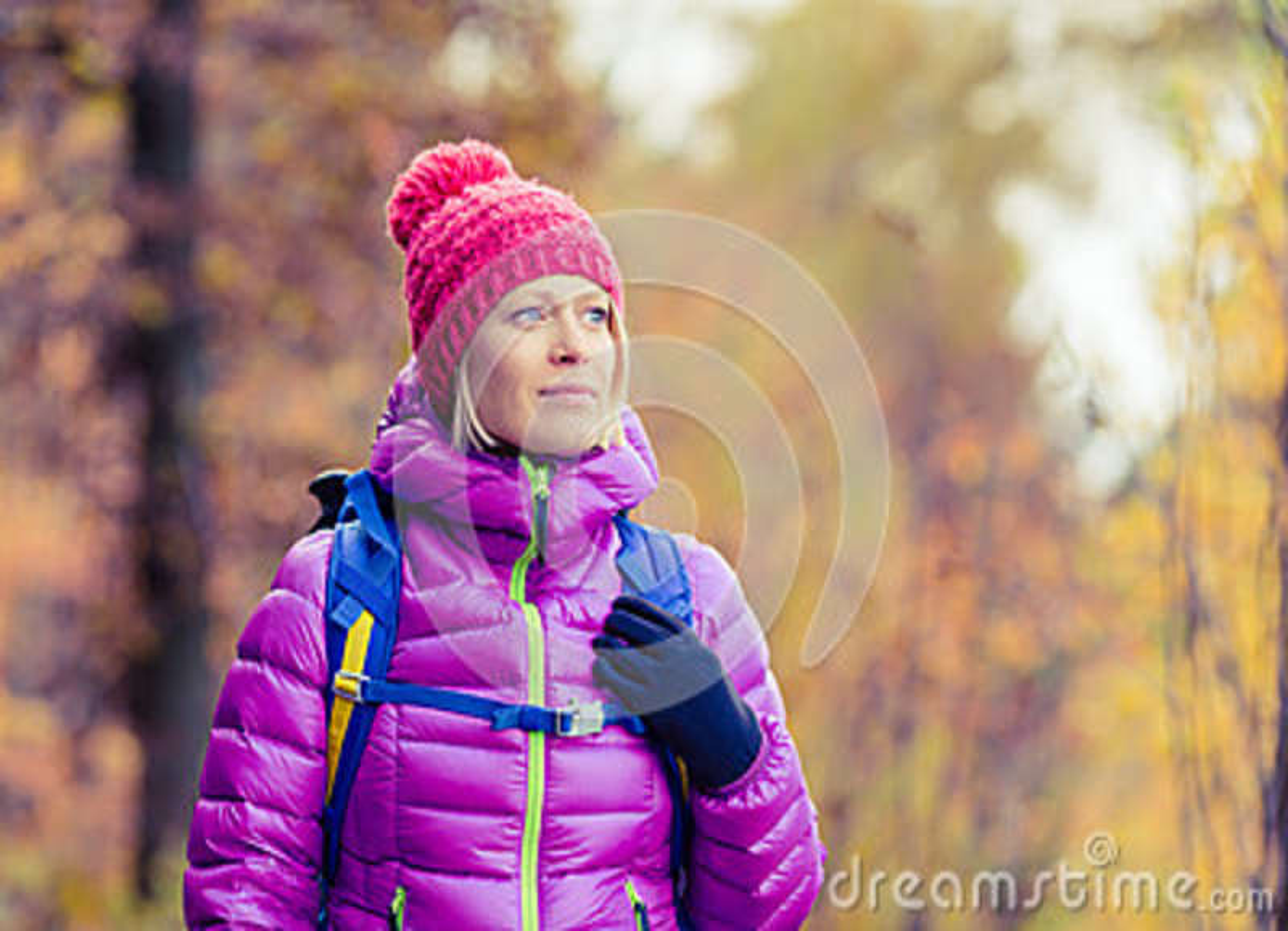 Wycieczkować kobiety patrzeje kamerę w inspiracyjnym au z plecakiem