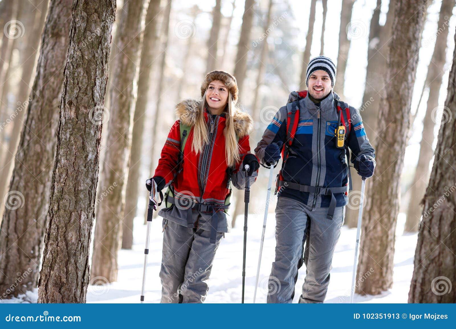 Wycieczkowicz para wycieczkuje w lesie w zimie