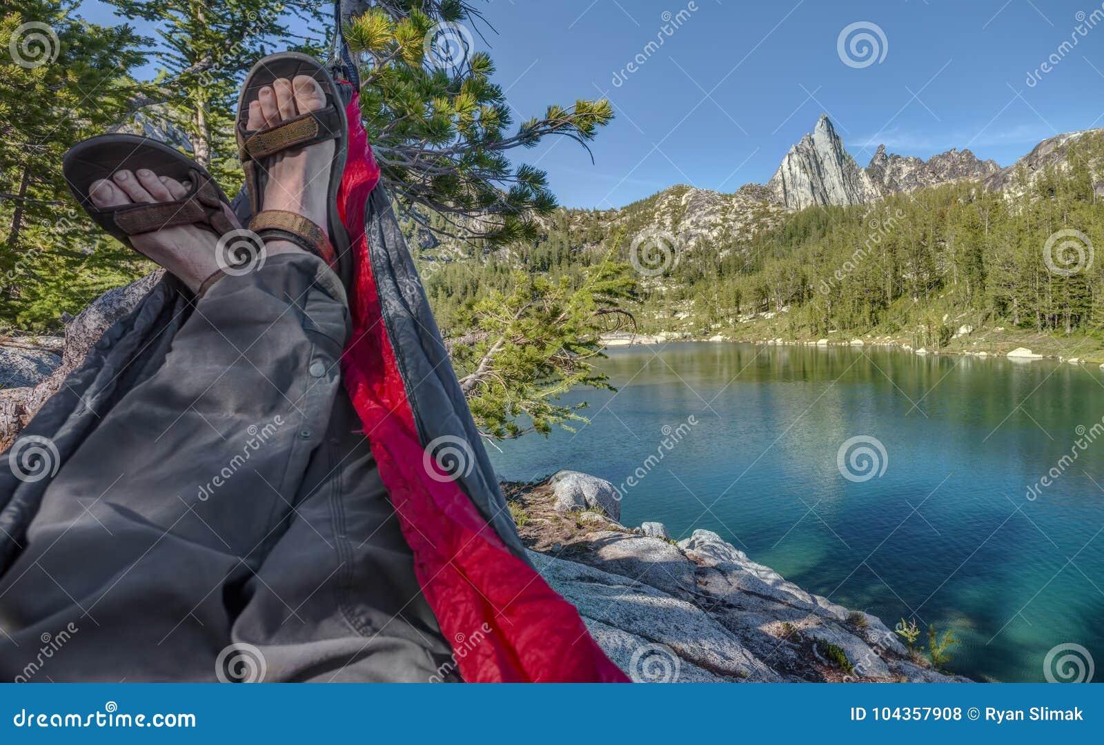 Wycieczkowiczy hole w hamaku nad Alpejskim jeziorem