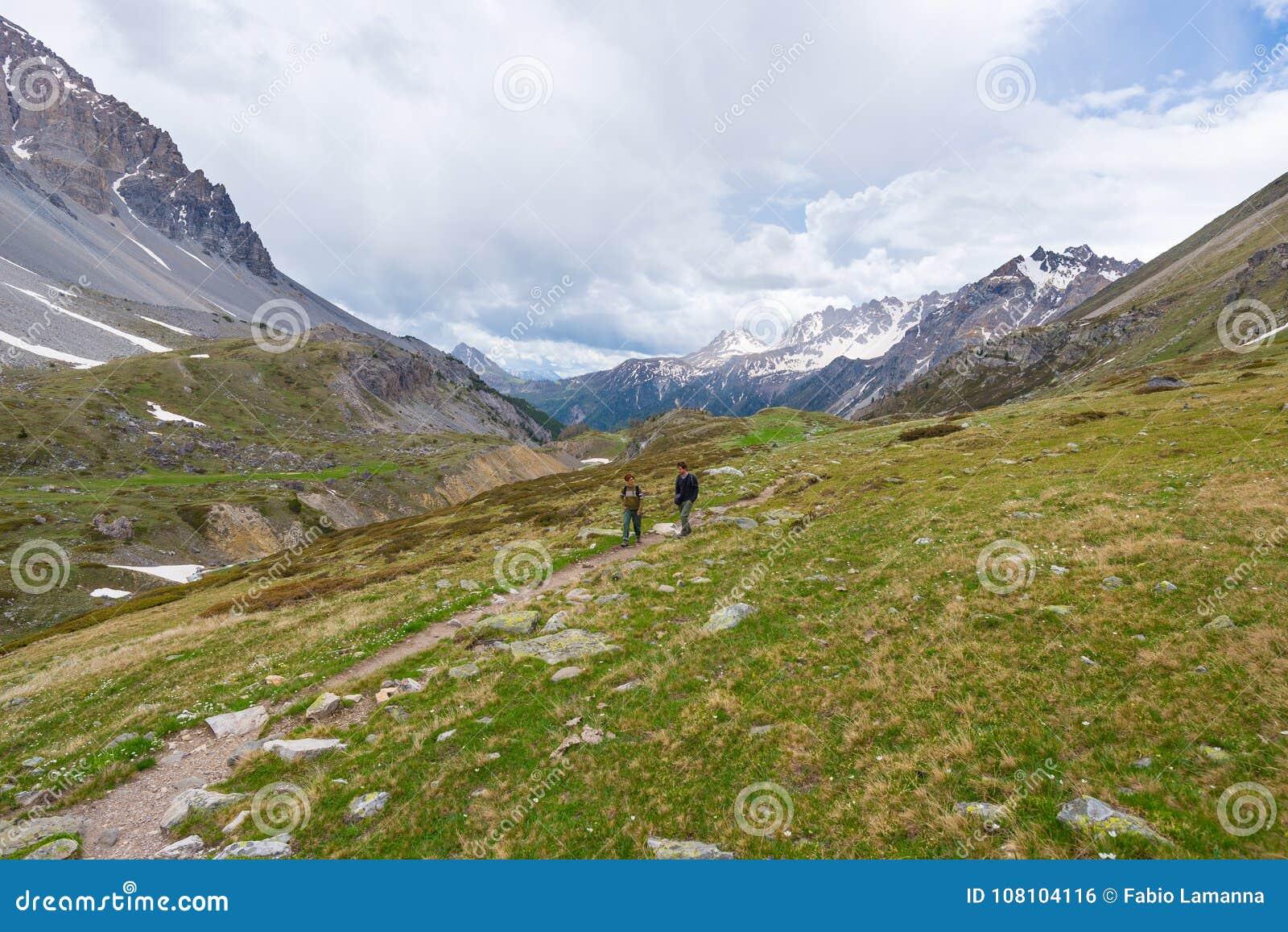 Wycieczkowiczy wspinać się ciężki na stromym skalistym halnym śladzie Lato eksploracja na Alps i przygody Dramatyczny niebo z bur