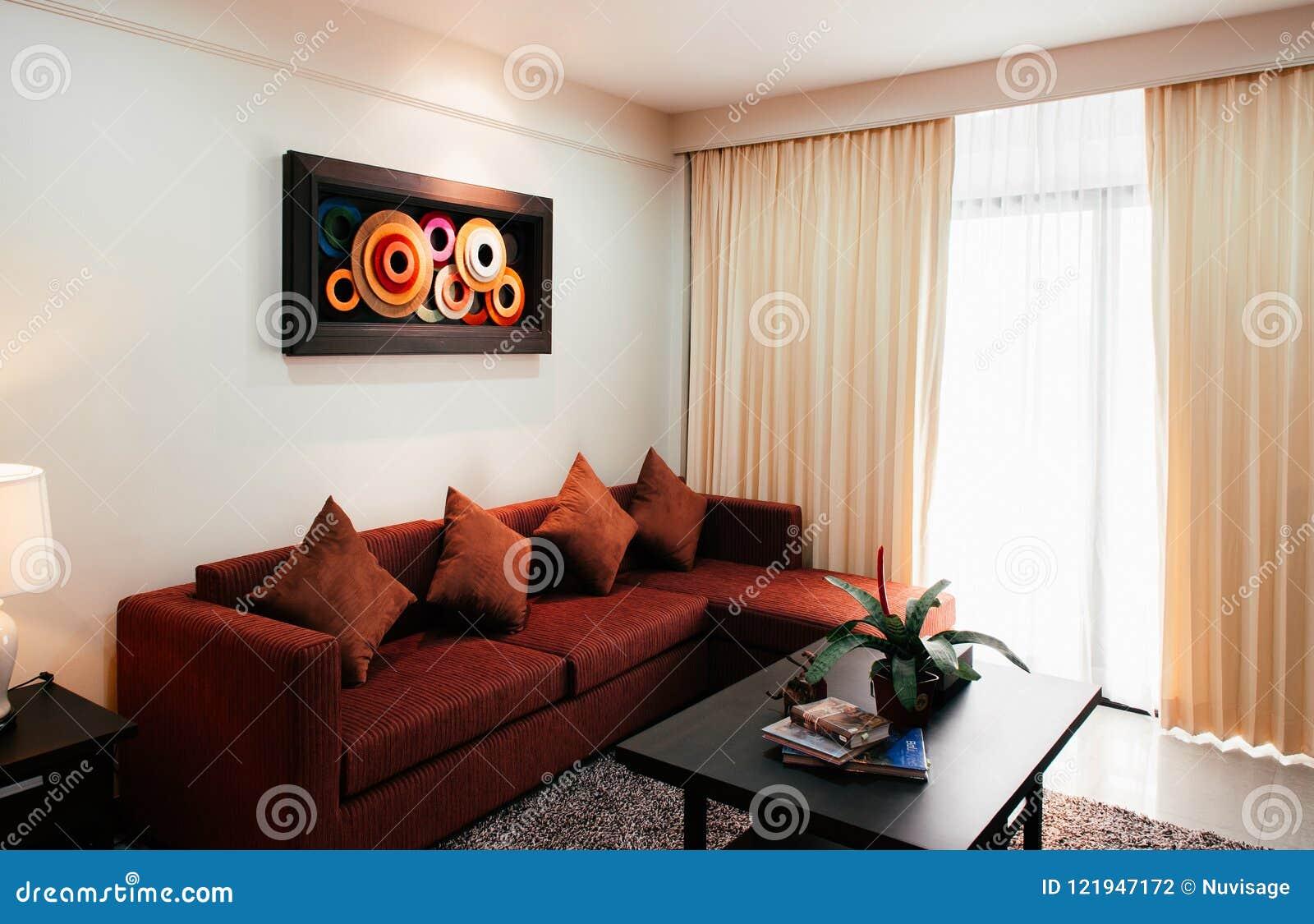 Wygodny żywy pokój z nowożytną obraz ścianą dekoracyjną i czerwoną w ten sposób