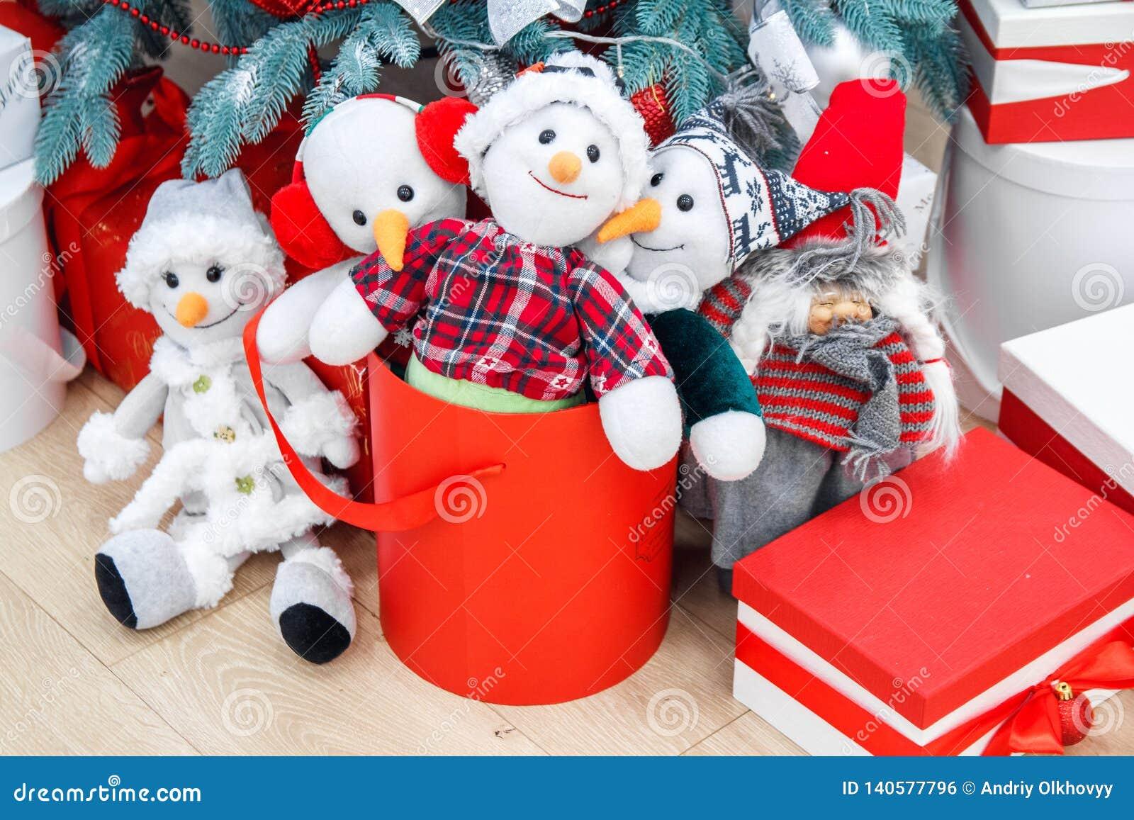 Wygodny zima wakacji tło Śmieszni zabawkarscy bałwany i teraźniejszość czeka boże narodzenia pod dekorującym jedlinowym drzewem r