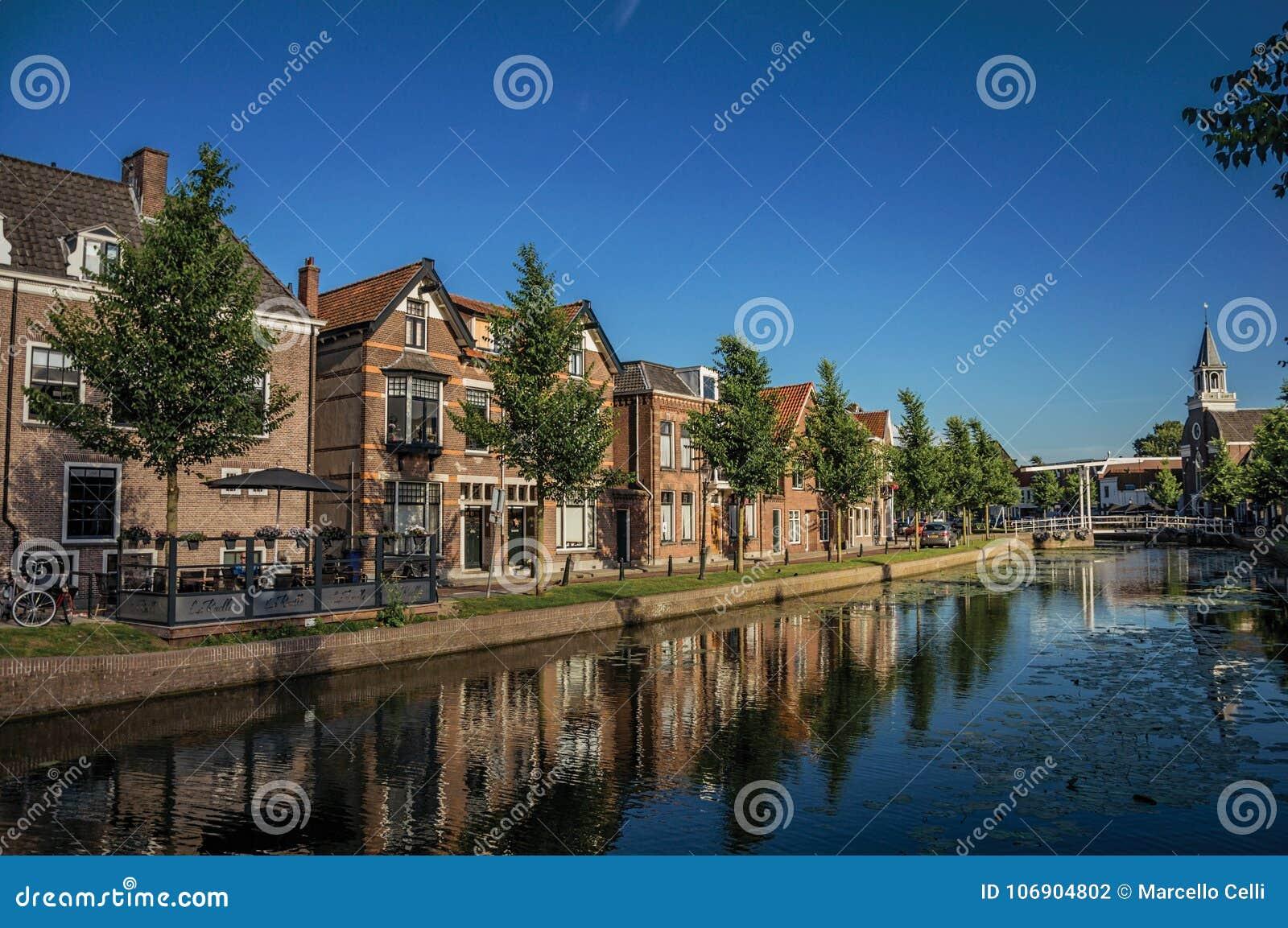 Wykładający kanał, kościelny dzwonkowy wierza i cegła domy na zmierzchu w Weesp,